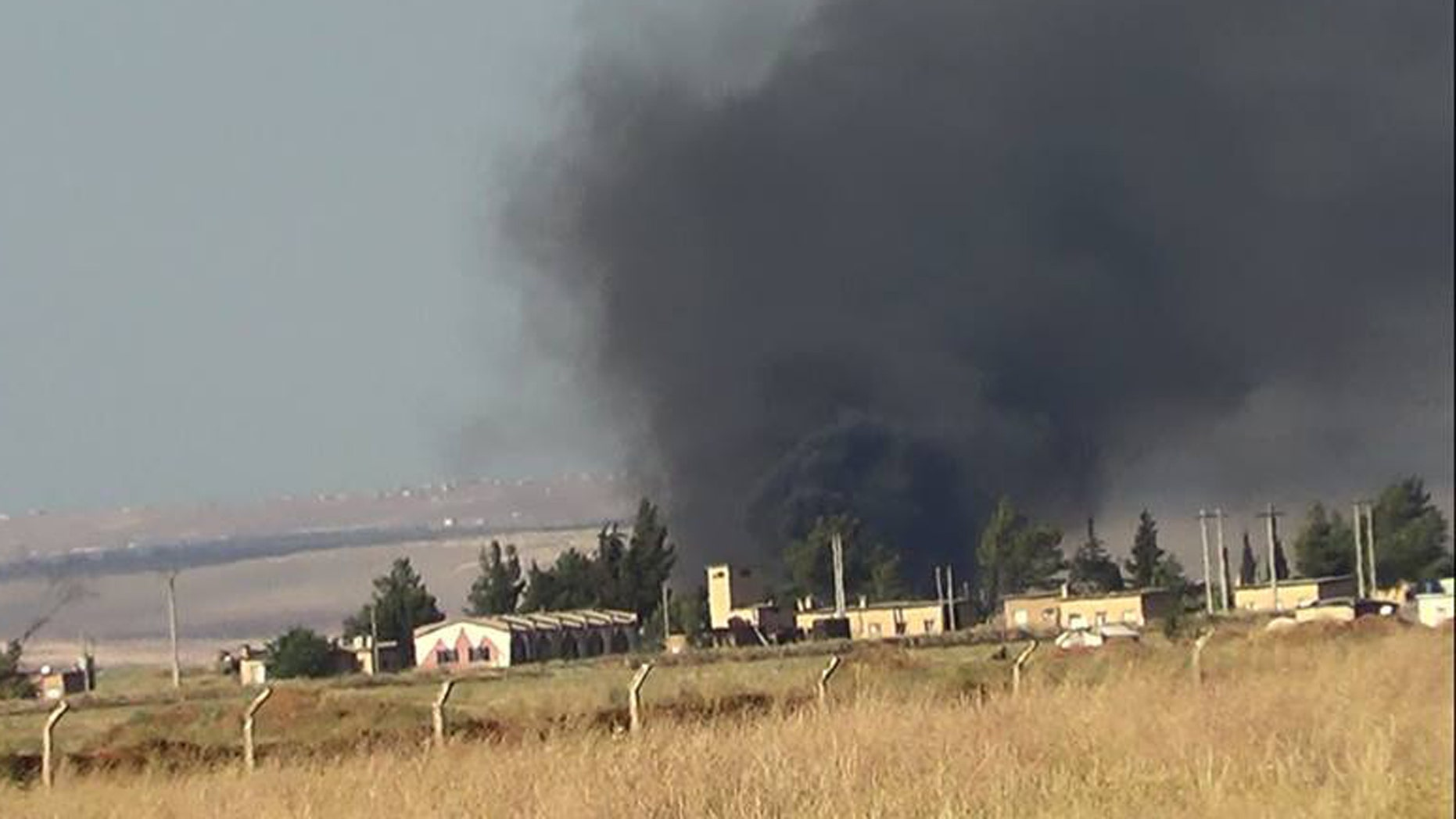 This citizen journalism image provided by Edlib News Network, ENN, which has been authenticated based on its contents and other AP reporting, shows black smoke rising from what rebels say is a helicopter that was shot down at Abu Dhour military airbase which is besieged by the rebels, in the northern province city of Idlib, Syria, Friday May 17, 2013. Rights activists have found torture devices and other evidence of abuse in government prisons in the first Syrian city to fall to the rebels, Human Rights Watch said in a report Friday. (AP Photo/Edlib News Network ENN)