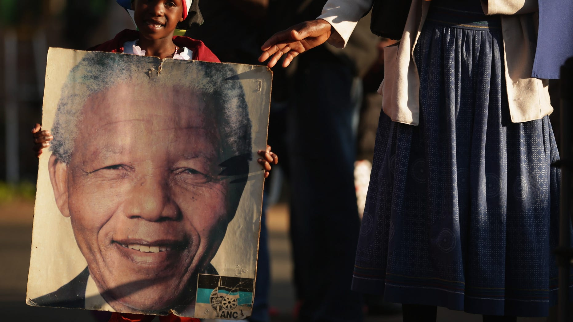 PRETORIA, SOUTH AFRICA - JULY 03:  Lehlogonolo Nkosi, 7, carries a photograph of former South African President Nelson Mandela outside the Mediclinic Heart Hospital where Mandela is being treated for a recurring lung infection July 3, 2013 in Pretoria, South Africa. The anti-apartheid icon and Nobel Peace Prize laureate has been in critical condition at the hospital for more than three weeks.  (Photo by Chip Somodevilla/Getty Images)