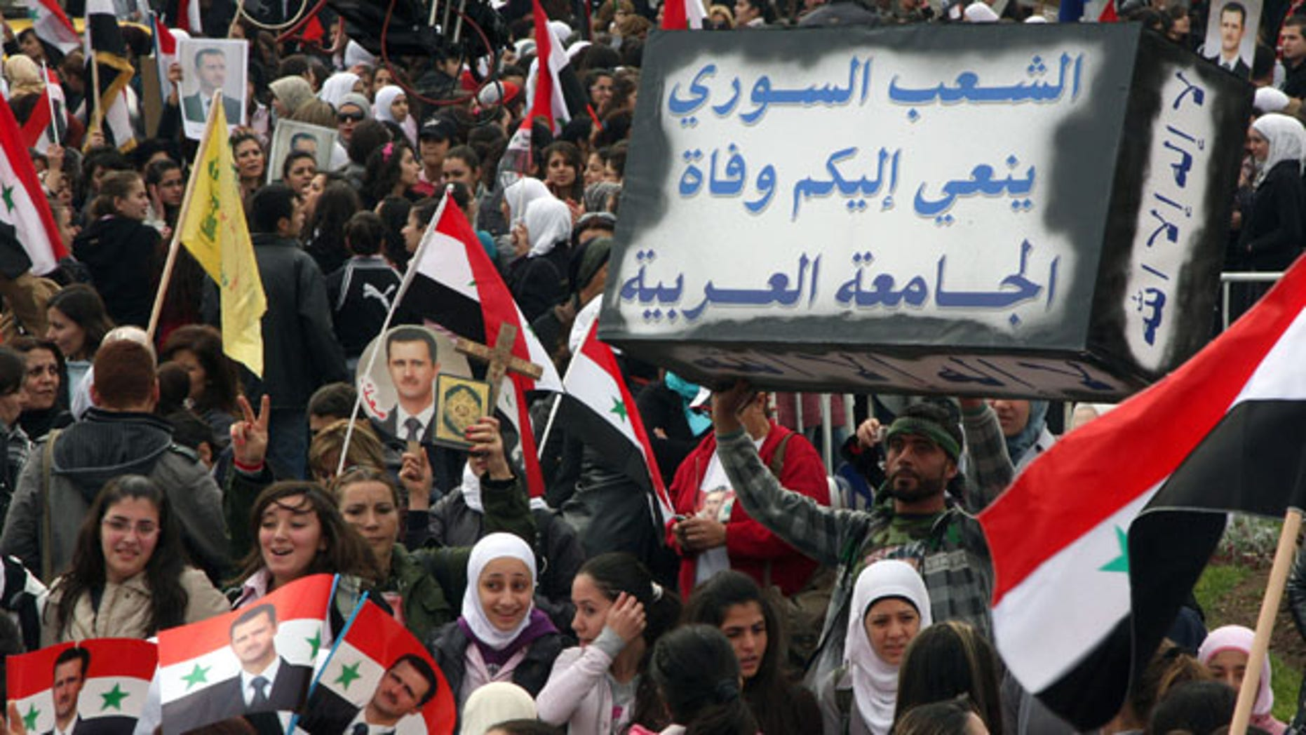 Nov. 24: Pro-Syrian regime protesters shout slogans as one holds a mock coffin with  Arabic words reading: 'The Syrian people announce to you the death of the Arab League,' during a protest against the Arab League meeting, in Damascus, Syria.