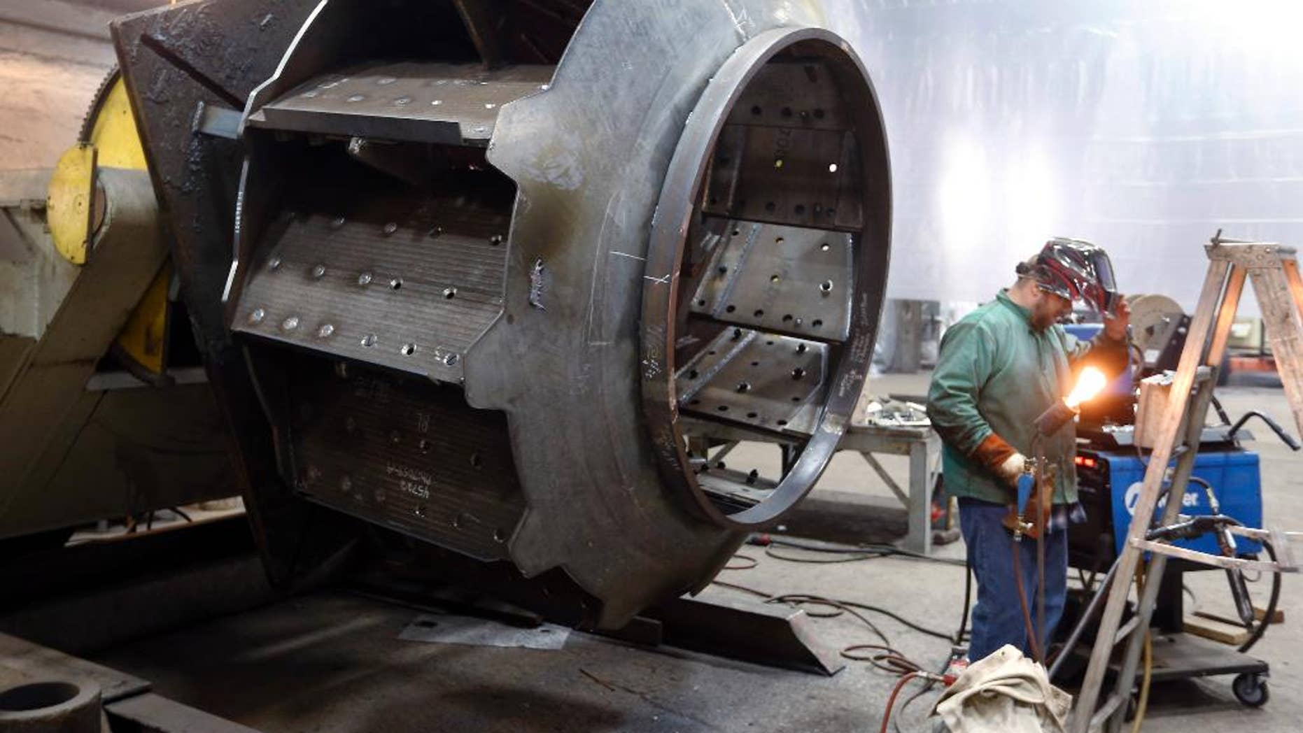 In this photo taken on Thursday, Feb. 12, 2015, a man welds parts in fans for industrial ventilation systems at the Robinson Fans Inc. plant in Harmony, Pa. The Commerce Department releases second-quarter gross domestic product on Thursday, July 30, 2015. (AP Photo/Keith Srakocic)