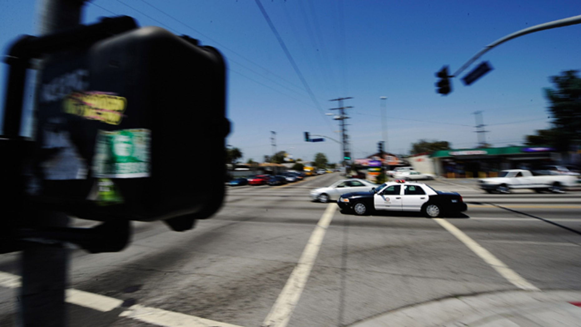 LOS ANGELES, CA - APRIL 27:  A Los Angeles Police Department car with lights and sirens going rushes through the intersection at Florence and Normandy Avenues in South Los Angeles on April 27, 2012 in Los Angeles, California. The intersection was the scene of the beating of truck driver Reginald Denny on April 29, 1992 during the early stages of the Los Angeles riots. It's been 20 years since the Rodney King verdict that sparked the riots.  (Photo by Kevork Djansezian/Getty Images)