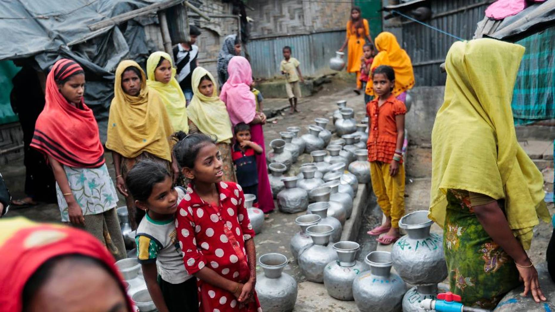 In this Dec. 3, 2016, record photo, Rohingya women and children wait to collect H2O during a Leda camp, an unregistered stay for Rohingya in Teknaf, nearby Cox's Bazar, a southern coastal district south of Dhaka, Bangladesh.