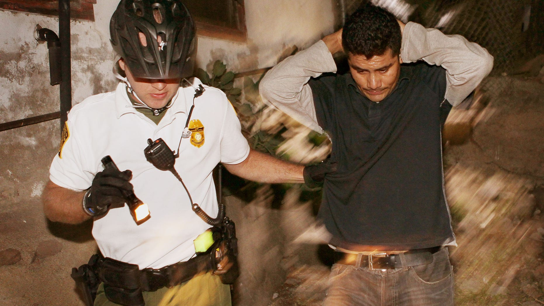 NOGALES, AZ - JUNE 02:  An U.S. Customs and Border Protection bike patrol agent apprehends an undocumented immigrant after he was spotted entering the country illegally June 2, 2010 in Nogales, Arizona. He was captured in the back yard of a home about one block from the border fence. During the 2009 fiscal year 540,865 undocumented immigrants were apprehended entering the United States illegally along the Mexican border, 241,000 of those were captured in the 262 mile stretch of the border known as the Tucson Sector.  (Photo by Scott Olson/Getty Images)