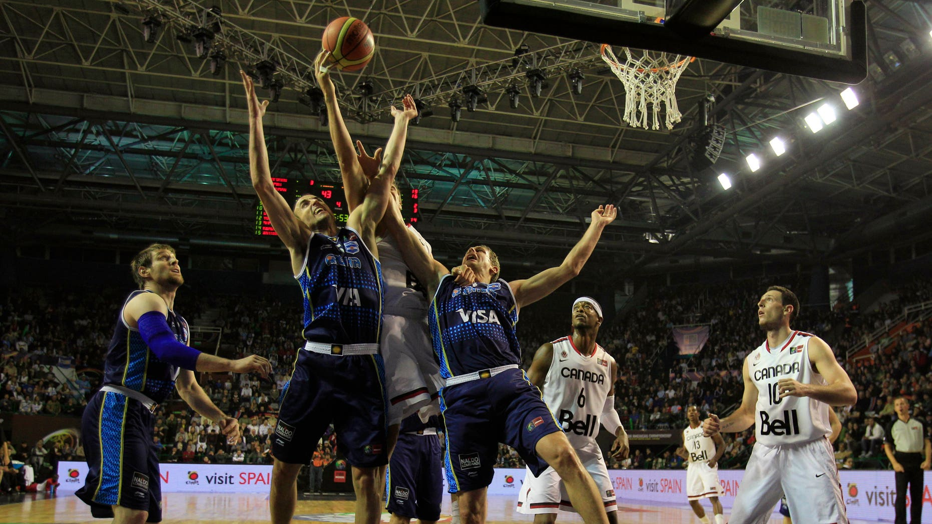 Argentina's players and Canada's players fight for possession during a FIBA Americas Championship basketball game in Mar del Plata, Argentina, Monday, Sept. 5, 2011. The top two finishers of the tournament get an automatic berth in the 2012 London Olympics and the next three advance to the last-chance Olympic qualifier to be held in July 2012. (AP Photo/Martin Mejia)