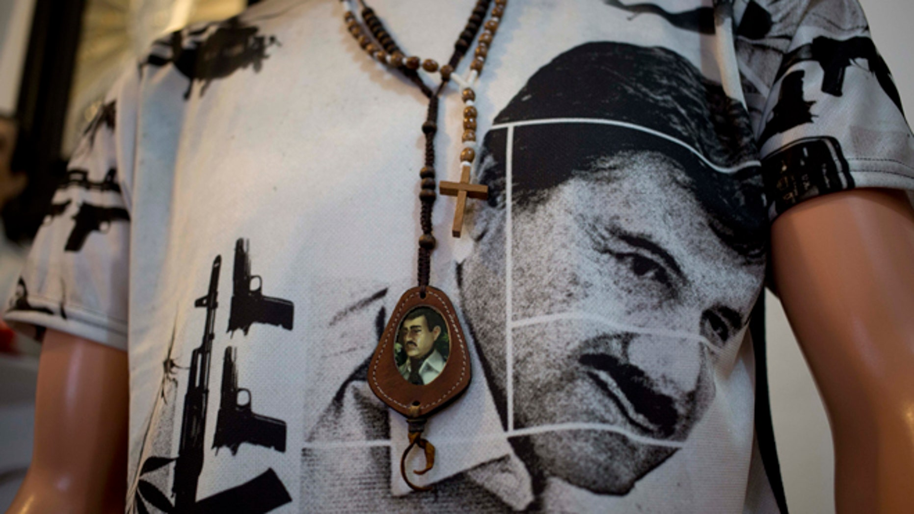 """A T-shirt of fugitive Mexican drug lord Joaquin """"El Chapo"""" Guzman covers a mannequin representing Jesus Malverde, known in Mexico as the """"Saint"""" of drug traffickers, inside the shrine of a faith healer in Mexico City, Friday, Oct. 16, 2015. The government is offering a reward of 60 million pesos, or about $3.5 million dollars, for Guzman's recapture after he made his second escape from a maximum security prison through an underground tunnel in 2015. (AP Photo/Eduardo Verdugo)"""