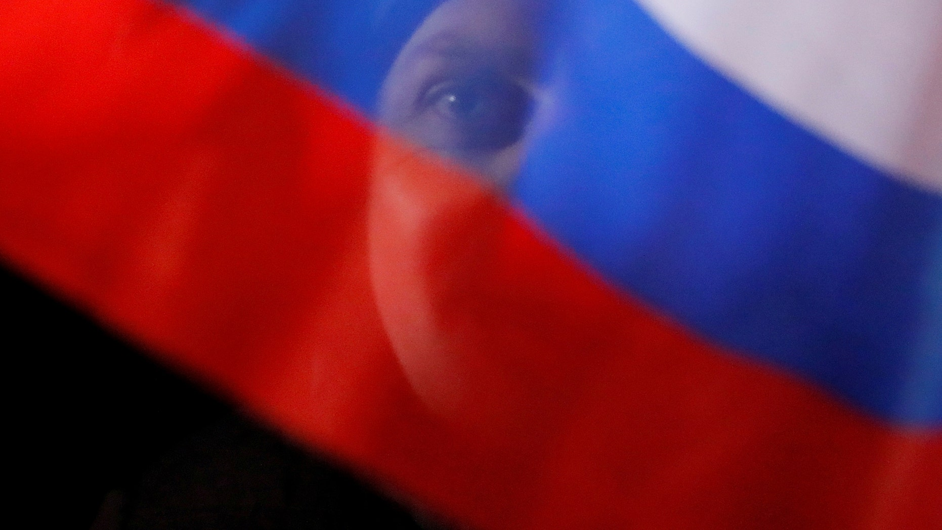 A man waves Russian flag during a rally and concert marking the fourth anniversary of Russia's annexation of the Crimea region, at Manezhnaya Square in central Moscow, Russia March 18, 2018. REUTERS/Maxim Shemetov