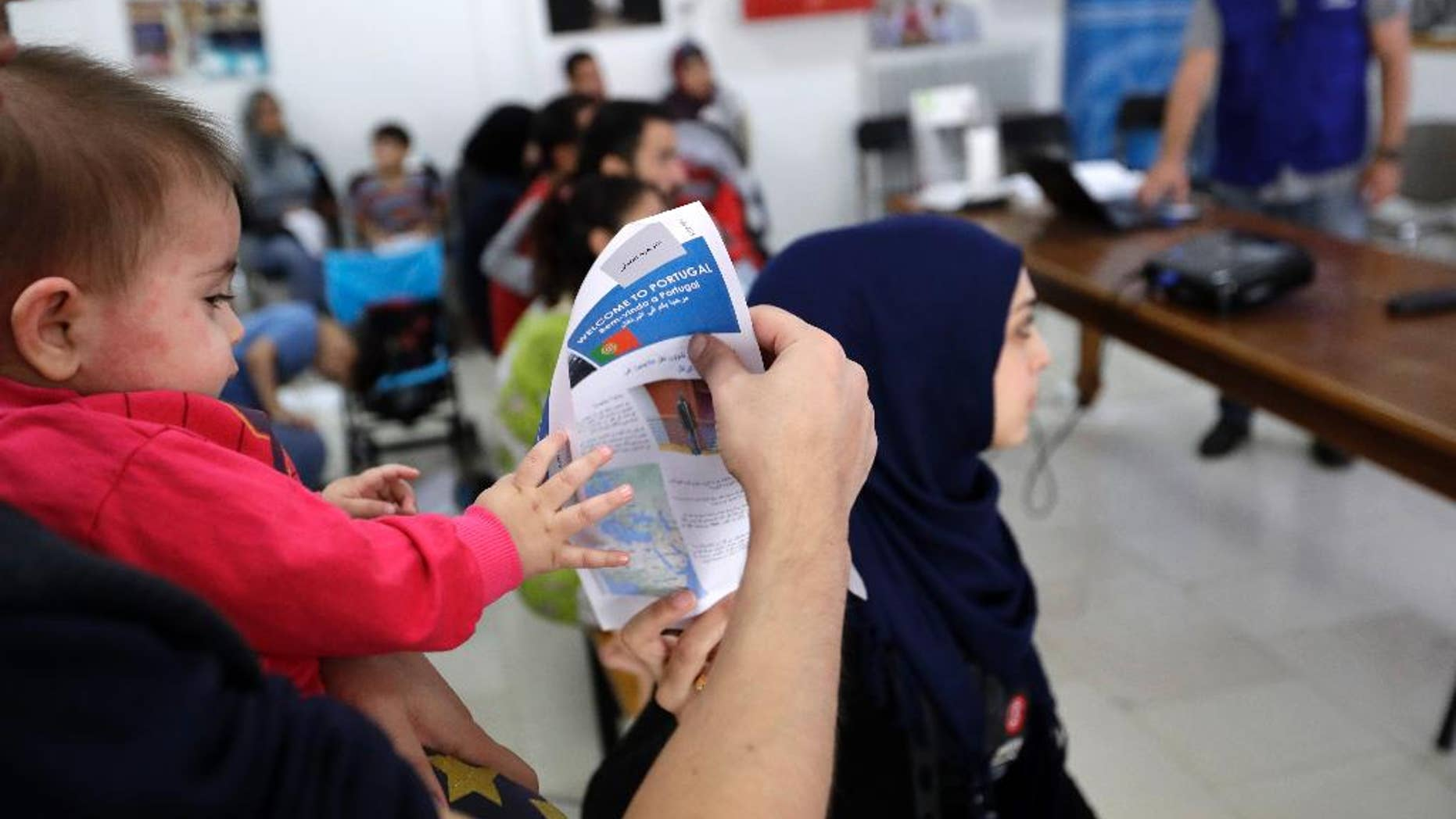 A child tries to takes a flyer from his father's hand as a group of 27 refugees takes part in an orientation program at International Organization of Migration office in Athens, Tuesday, Sept. 27, 2016, one day before being relocated to Portugal. The program should have seen 66,400 people from Greece relocated across the EU over two years from Sept. 16 last year, but to date just over 4,130 people have been resettled. (AP Photo/Thanassis Stavrakis)
