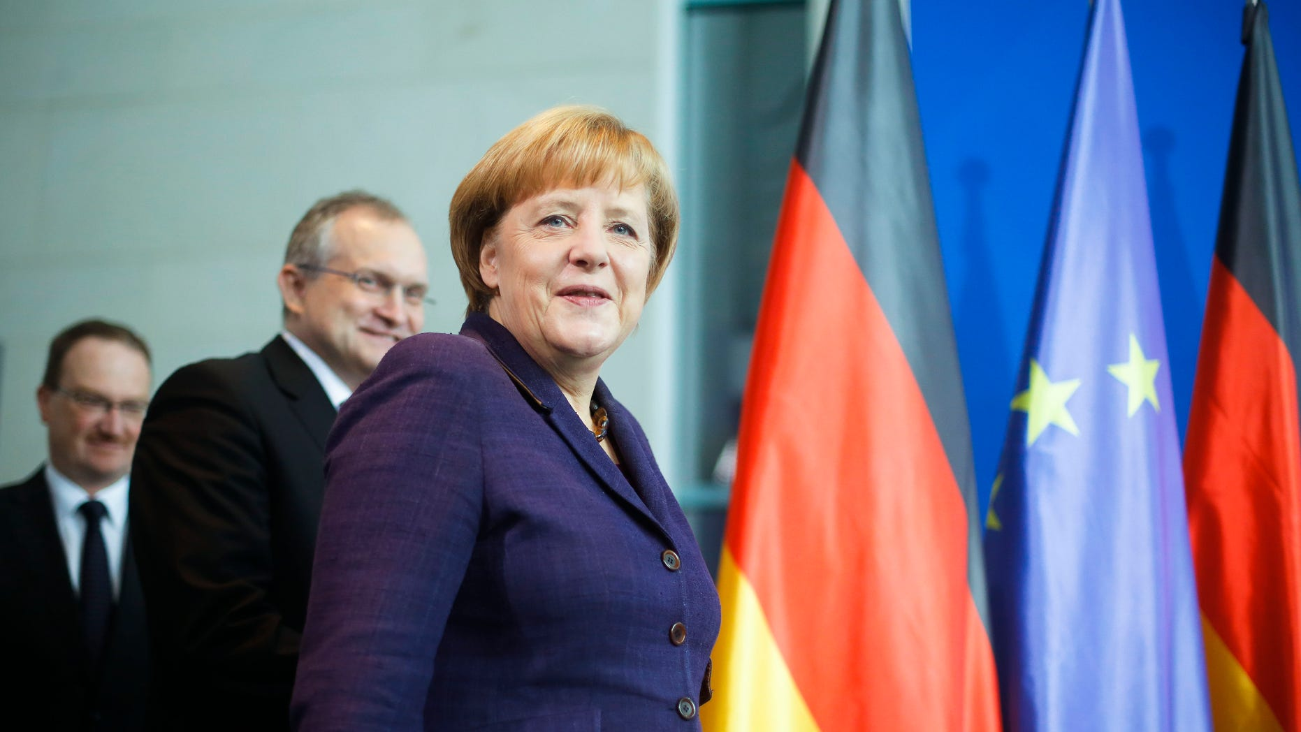 German Chancellor Angela Merkel is followed by economy advisers Lars Feld, left, and Christoph Schmidt, center, as they arrive for the hand-over ceremony of the prognosis for Germany's economy in the upcoming year at the chancellery in Berlin, Wednesday, Nov. 13, 2013. (AP Photo/Markus Schreiber)