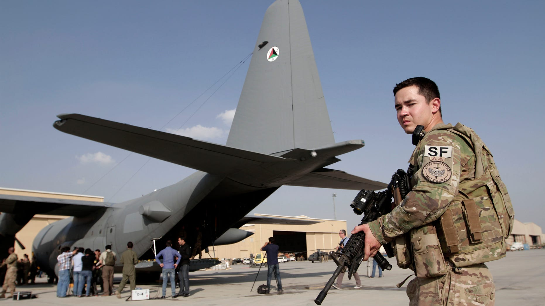 An International Security Assistance Force soldier stands guard near a C-130 transport aircraft at the Afghan Air Force Base in Kabul, Afghanistan, Wednesday, Oct. 9, 2013. Afghanistan took delivery on Wednesday of two C-130 transport aircraft from the United States, part of an effort to give the country's military the ability to better fight insurgents around the country. (AP Photo/Rahmat Gul)