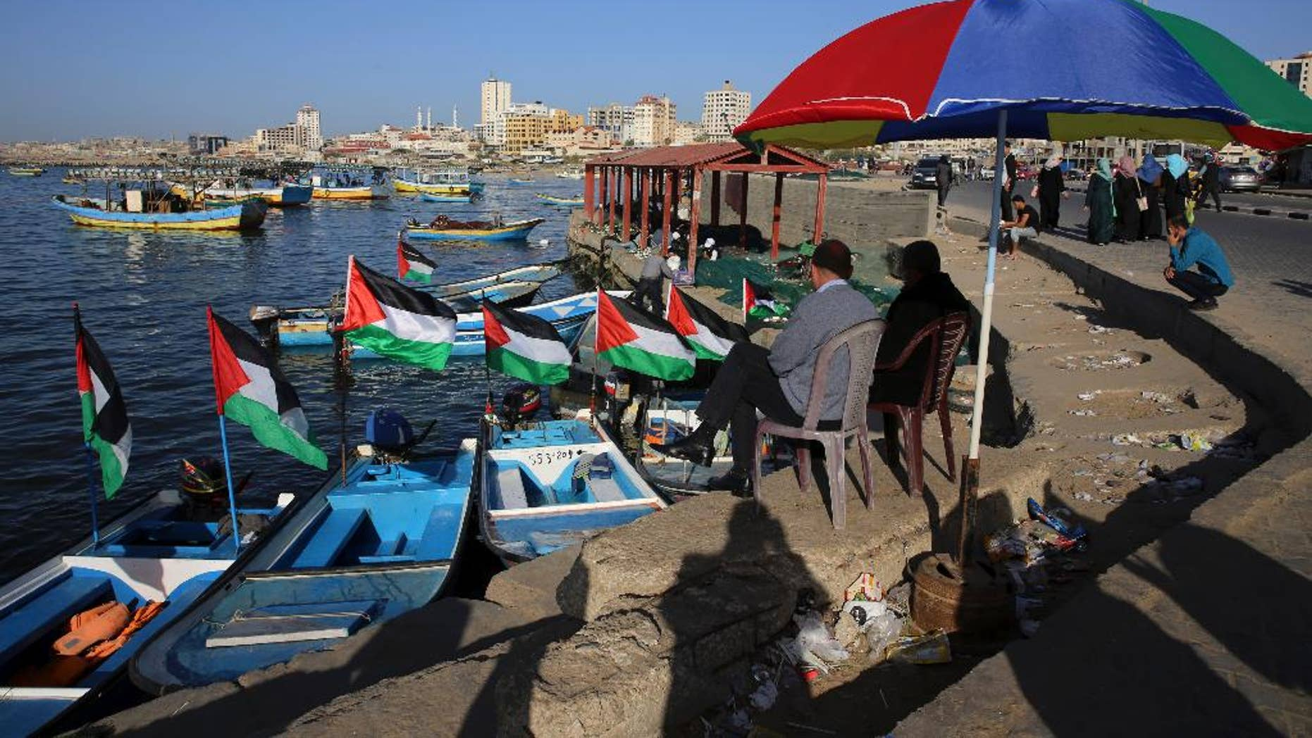 """File - In this Sunday, April 17, 2016 file photo, Palestinians protect themselves from the sun at the fishermen port in Gaza City. Israel's transportation minister Yisrael Katz said he is pushing for the construction of an """"artificial island"""" off the coast of Hamas-ruled Gaza to alleviate hardship in the blockaded coastal strip.With Israel and Egypt maintaining a naval blockade of Gaza, the Palestinians have long been pleading for a port to connect them to the rest of the world. (AP Photo/Adel Hana, File)"""