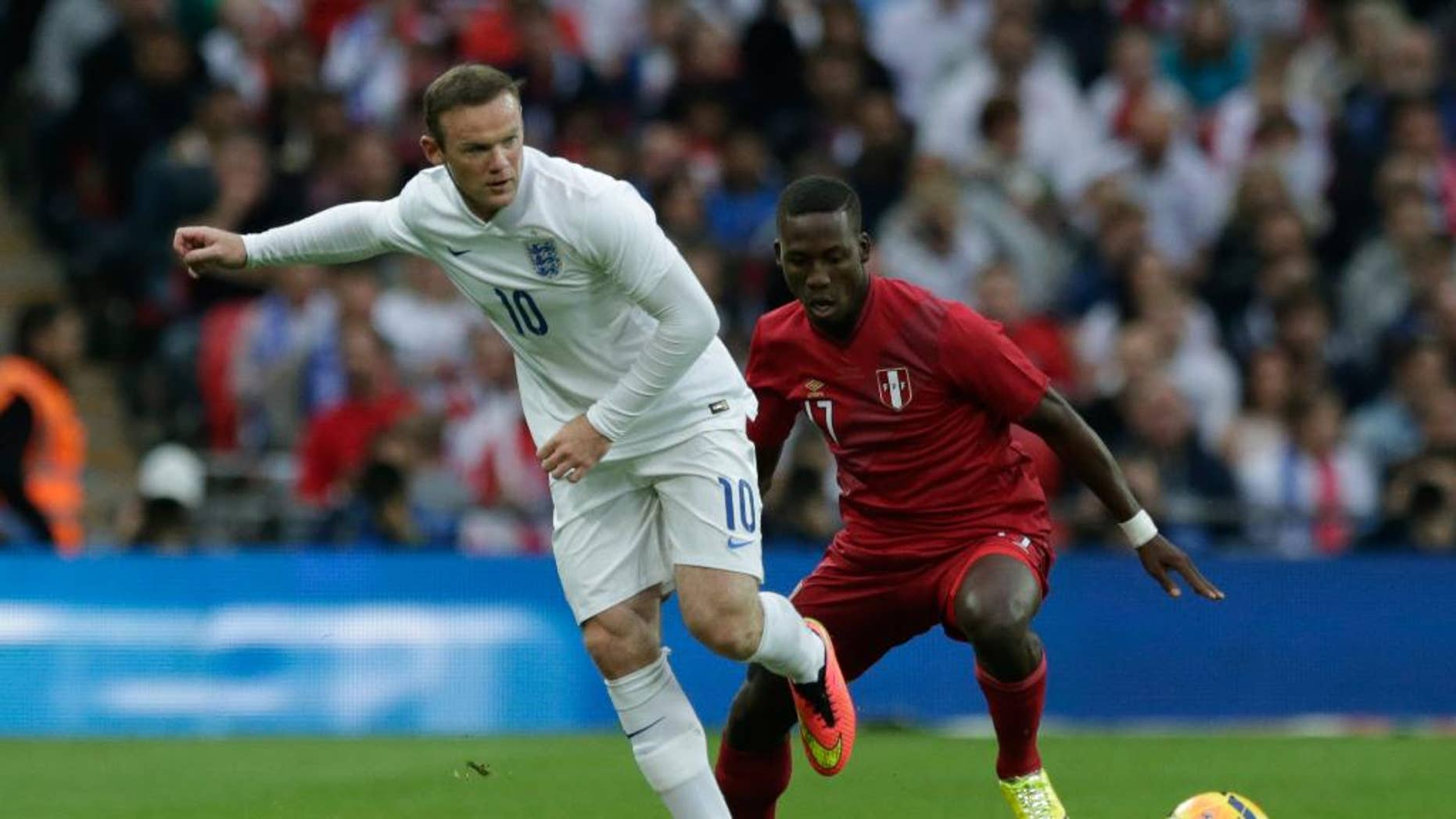 England's Wayne Rooney, left, competes for the ball with Peru's Luis Advincula during the international friendly soccer match between England and Peru at Wembley Stadium in London, Friday, May 30, 2014.  (AP Photo/Matt Dunham)
