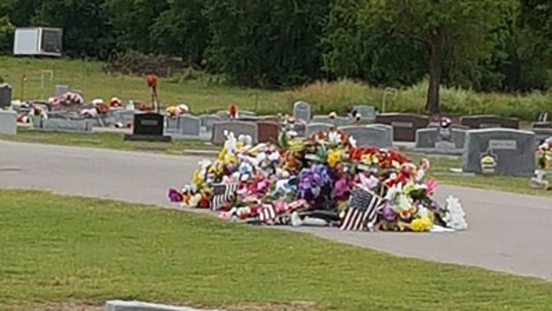 The flags were seen in a giant pile on the ground at Bixby Cemetery in Oklahoma.