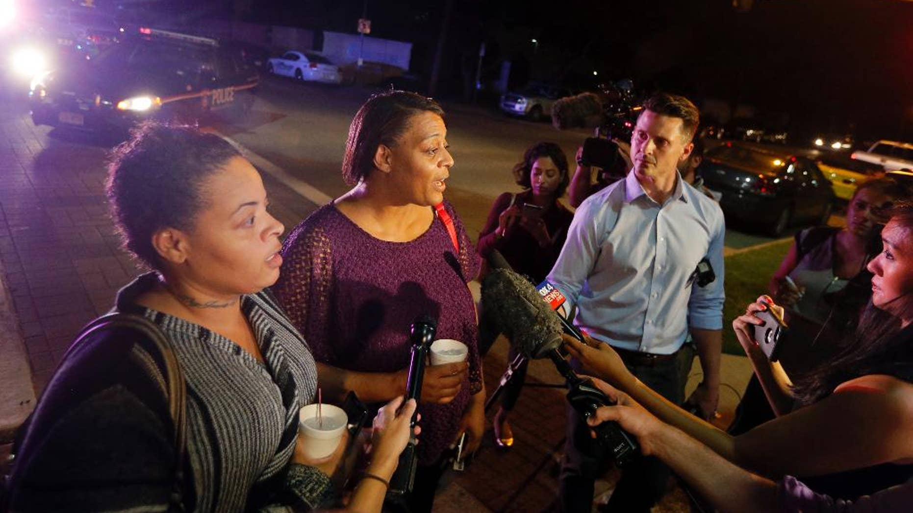CORRECTS SPELLING TO SHERIE - Sherie Williams, left, and Theresa Williams, center, speak to the media as they leave the Baylor University Medical Center, Friday, July 8, 2016, in Dallas. Theresa Williams said her sister Shetamia Taylor, who was attending a rally with her four teenage sons in downtown Dallas, was shot in one of her legs. (AP Photo/Tony Gutierrez)
