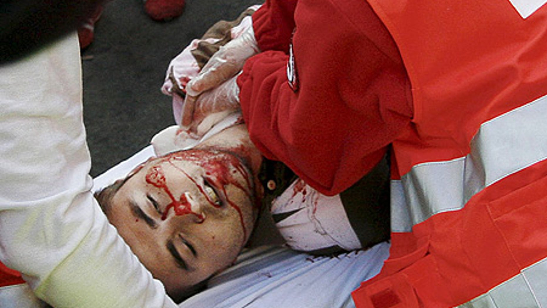 July 10: A reveler is taken away on a stretcher after being gored in the neck by a bull during the run, in Pamplona. He later died at hospital.