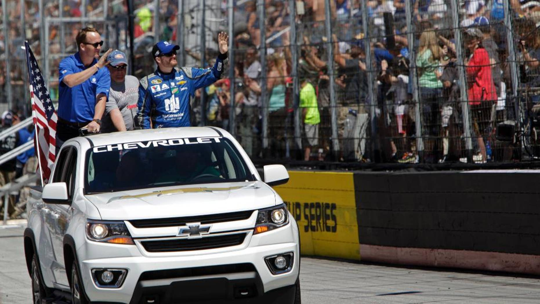 Former University of Tennessee and Denver Bronco's quarterback Peyton Manning, left, and driver Dale Earnhardt Jr. (88) wave to fans before a NASCAR Sprint Cup Series auto race, Sunday, April 17, 2016 in Bristol, Tenn. (AP Photo/Wade Payne)