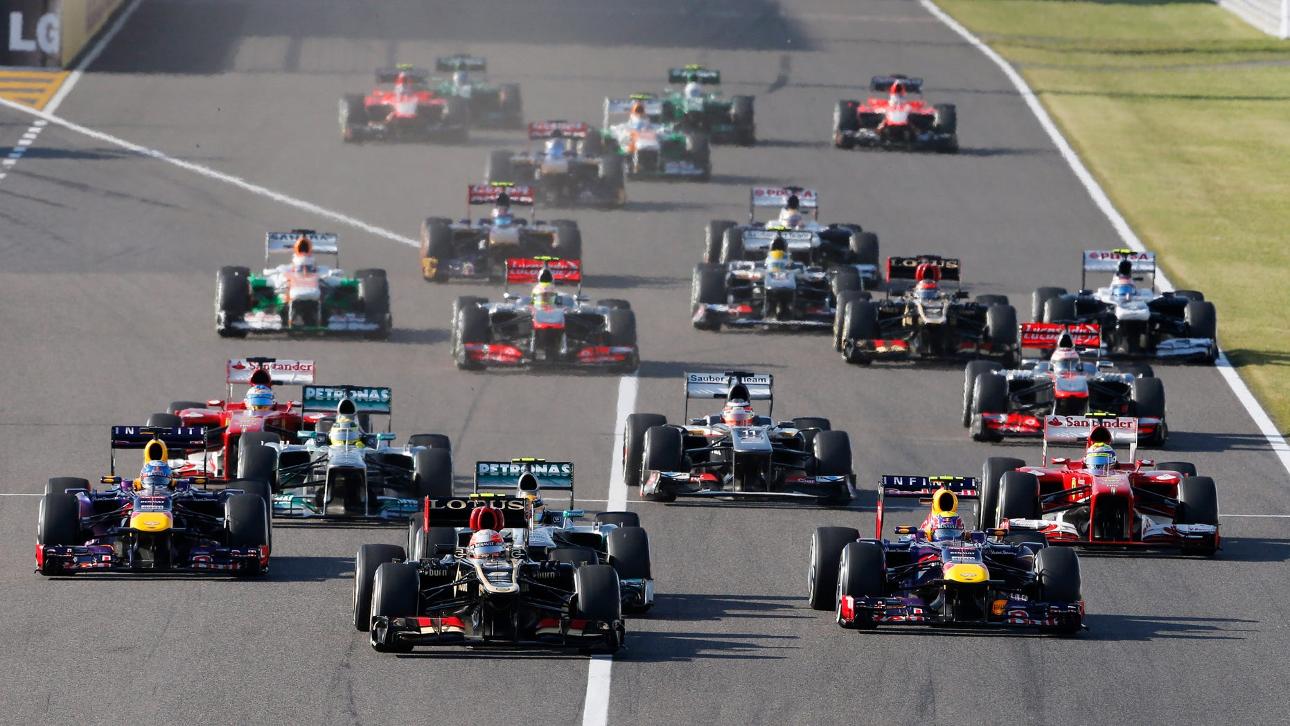 Lotus driver Romain Grosjean of France, center, leads Red Bull driver Mark Webber of Australia, front right, and Red Bull driver Sebastian Vettel of Germany, left, at the start of the Japanese Formula One Grand Prix at the Suzuka circuit in Suzuka, Japan, Sunday, Oct. 13, 2013. (AP Photo/Shuji Kajiyama)