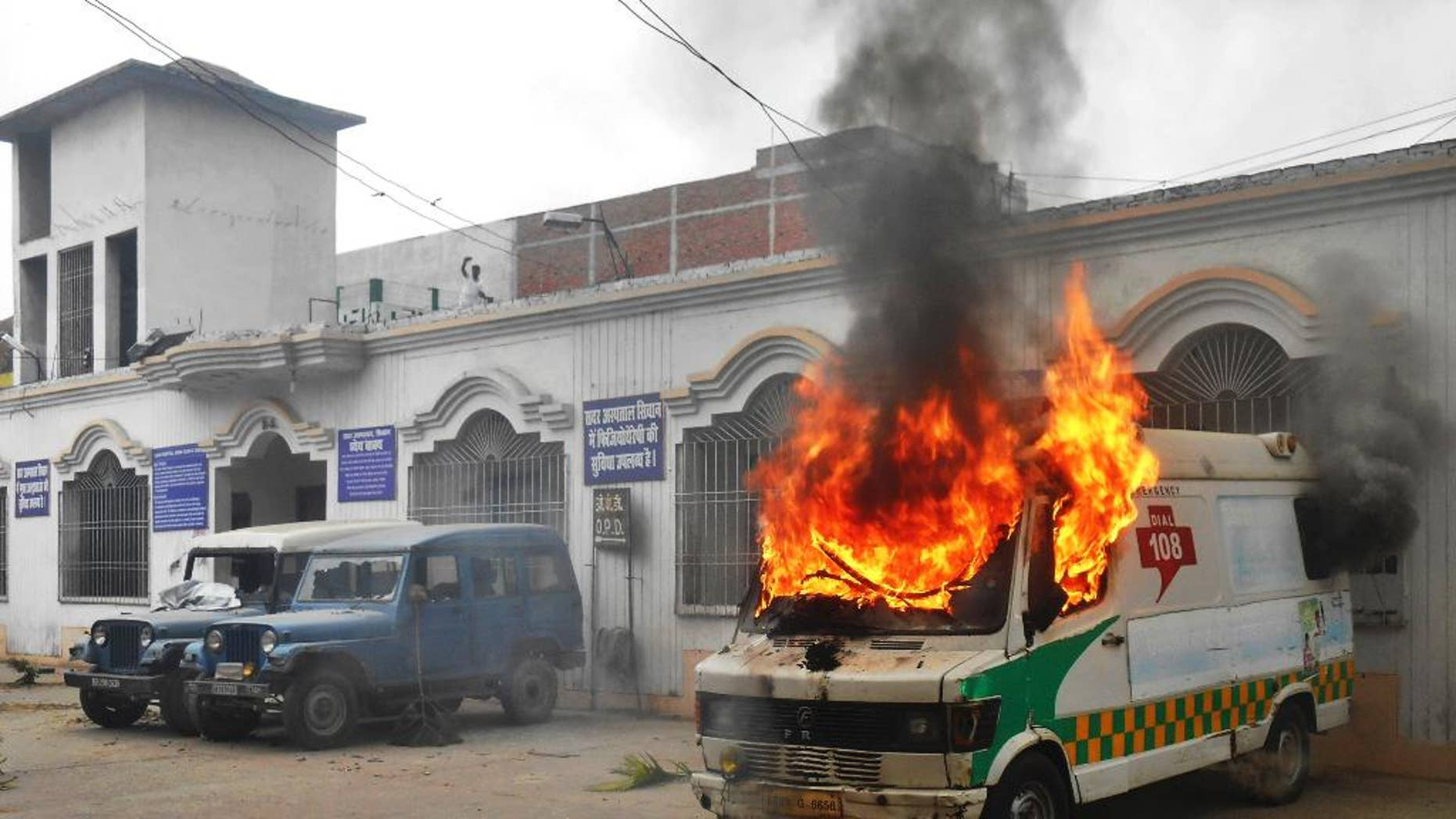An ambulance goes up in flames after it was set fire by angry villagers at a government hospital in Siwan, about 200 kilometers (125 miles) north of Patna, Bihar state, India, Monday, April 20, 2015. Villagers who took injured students of a road accident to this hospital became incensed when they discovered no doctors were present. About 100 people attacked the hospital in anger and burned six vehicles, including this ambulance. (AP Photo/Abhinav Patel)