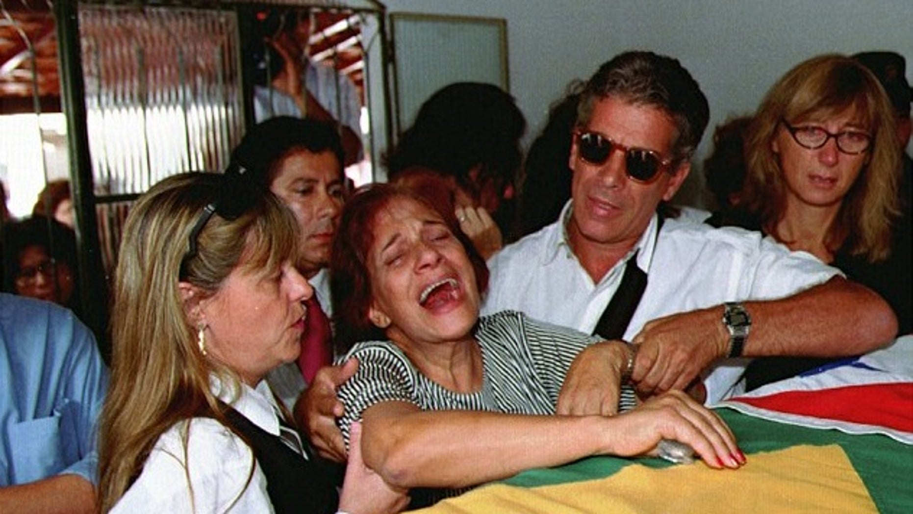Lidia Pinto Machado, center, mother of Maria Isabel Monteiro Alves, mourns over her daughter's coffin during funeral services in 1995.