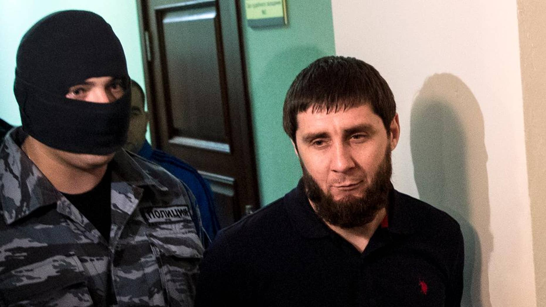 A police officer, left, escorts Zaur Dadaev, one of five suspects held in the killing of Russian opposition politician Boris Nemtsov, is escorted in a court in Moscow, Russia, Monday, Oct. 3, 2016. A Moscow military court is beginning to hear the case of five people accused of involvement in the killing of Nemtsov in February 2015. (AP Photo/Pavel Golovkin)