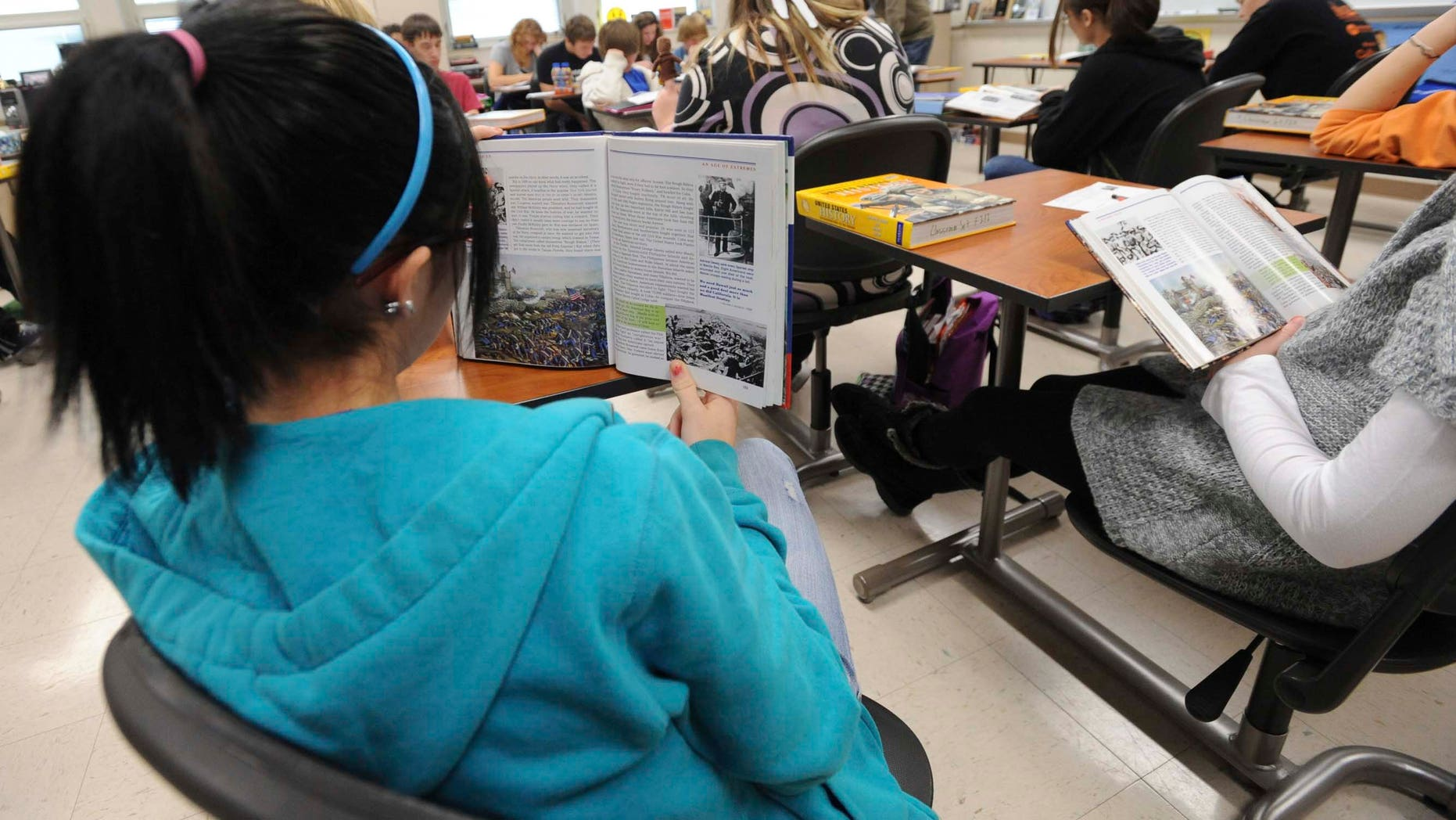 ** FOR USE MONDAY, Dec. 13 AND THEREAFTER** In this photo taken on Dec. 3, 2010, sophomore Ariel Russell follows along in her book as another student reads out loud in the John Jackson's U.S. history class at the Franklin High School in Franklin, Ind. School officials hope to give even more students a chance to earn college credits by making more dual-credit courses available. The goal is to get students who are planning to attend college a head start, as well as to give students the confidence that they can succeed in college level courses. (AP Photo/Daily Journal, Scott Roberson)
