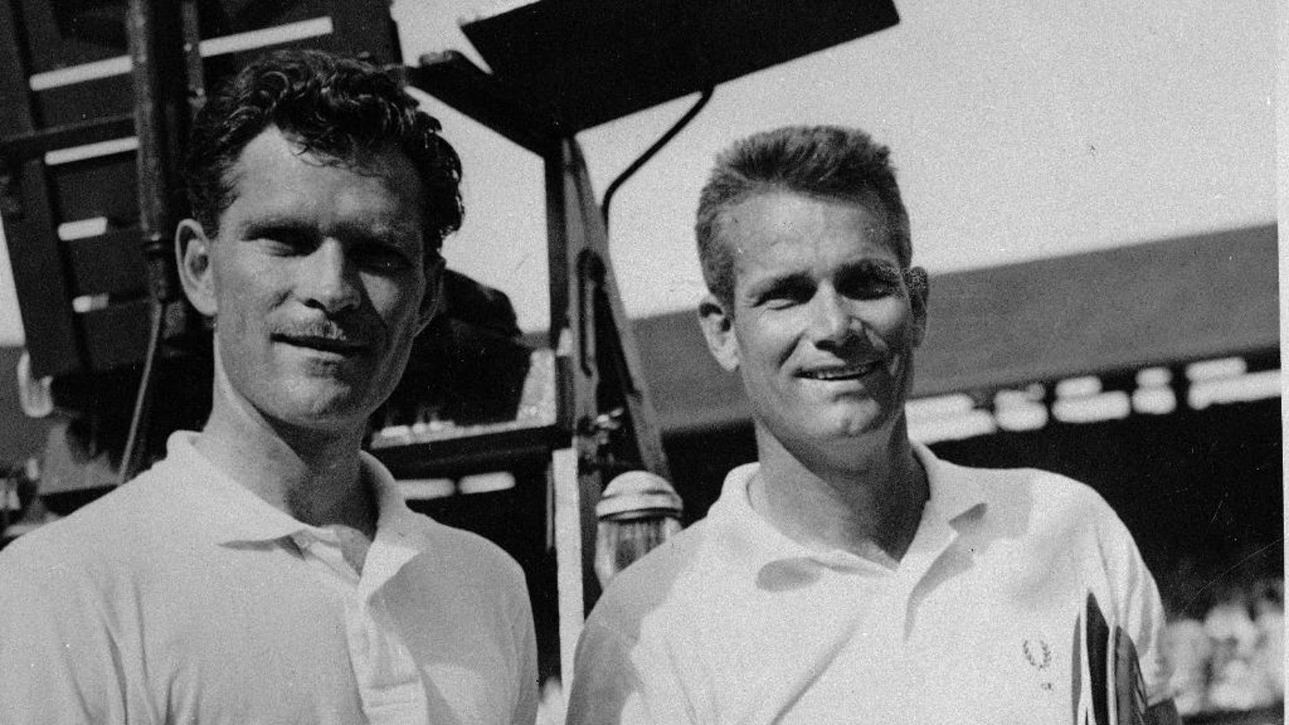 FILE - In this July, 6, 1957, file photo, winning doubles partners Budge Patty, left, and Gardnar Mulloy, both of the United States, hold their trophies after being presented by Queen Elizabeth at Wimbledon. Mulloy, a member of the International Tennis Hall of Fame who won 129 U.S. national titles, died Monday night, Nov. 14, 2016, in Miami. He was 102. (AP Photo/File)