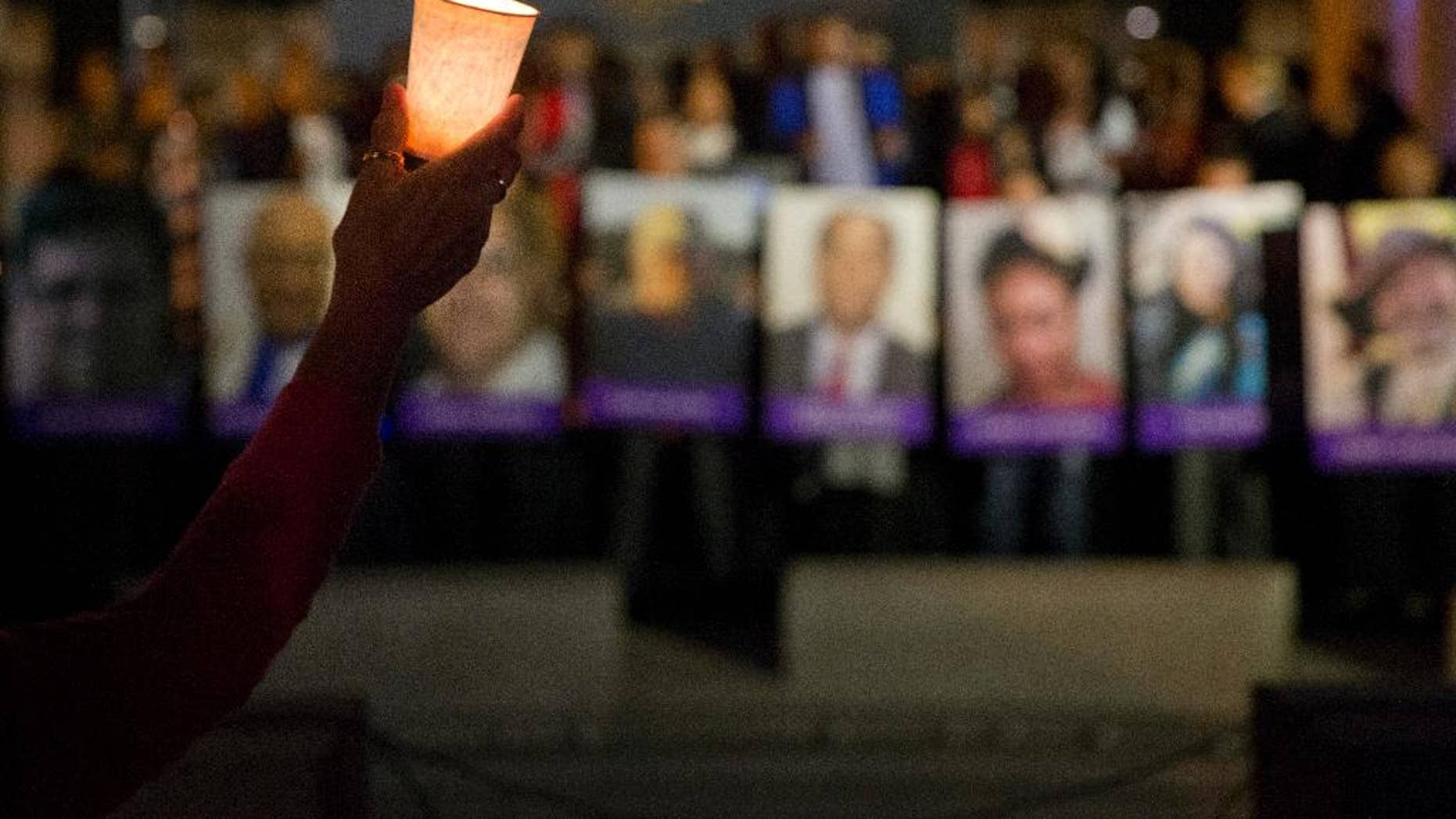 FILE - In this Dec. 7, 2015, file photo, Arlene Payan holds a candle during a vigil to honor shooting victims in San Bernardino, Calif. The shootings in San Bernardino are a reminder of how vulnerable workplaces can be. Companies have called security consultants, human resources providers and attorneys since the attack, seeking information about what to do if there's a shooter on their premises. Companies that already have plans in place are reviewing them to see what changes they need to make. (AP Photo/Jae C. Hong, File)