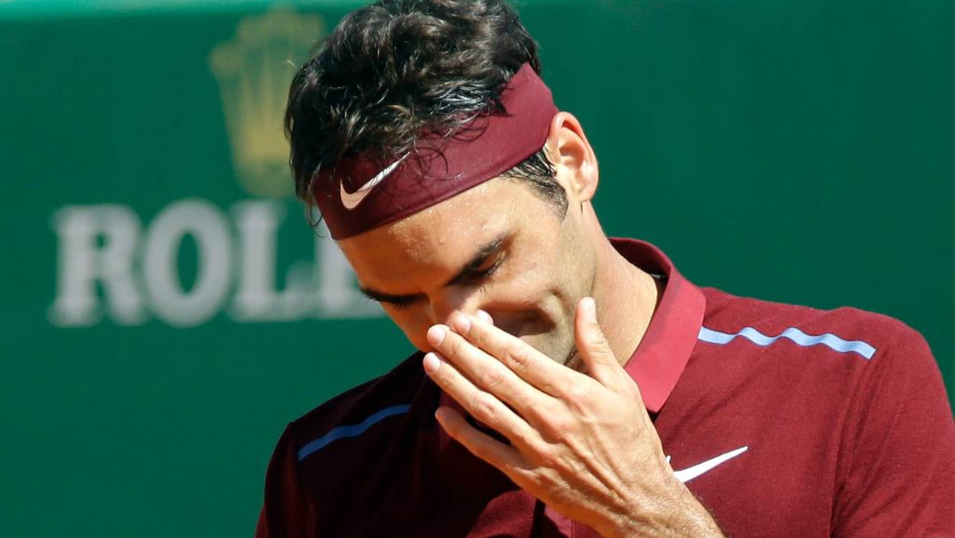 FILE- In this April 15, 2016 file photo, Swiss Roger Federer gestures during his quarter final match of the Monte Carlo Tennis Masters tournament against France's Jo-Wilfried Tsonga, in Monaco. Roger Federer withdrew from the Madrid Masters on Monday because of a back injury. (AP Photo/Lionel Cironneau, File)