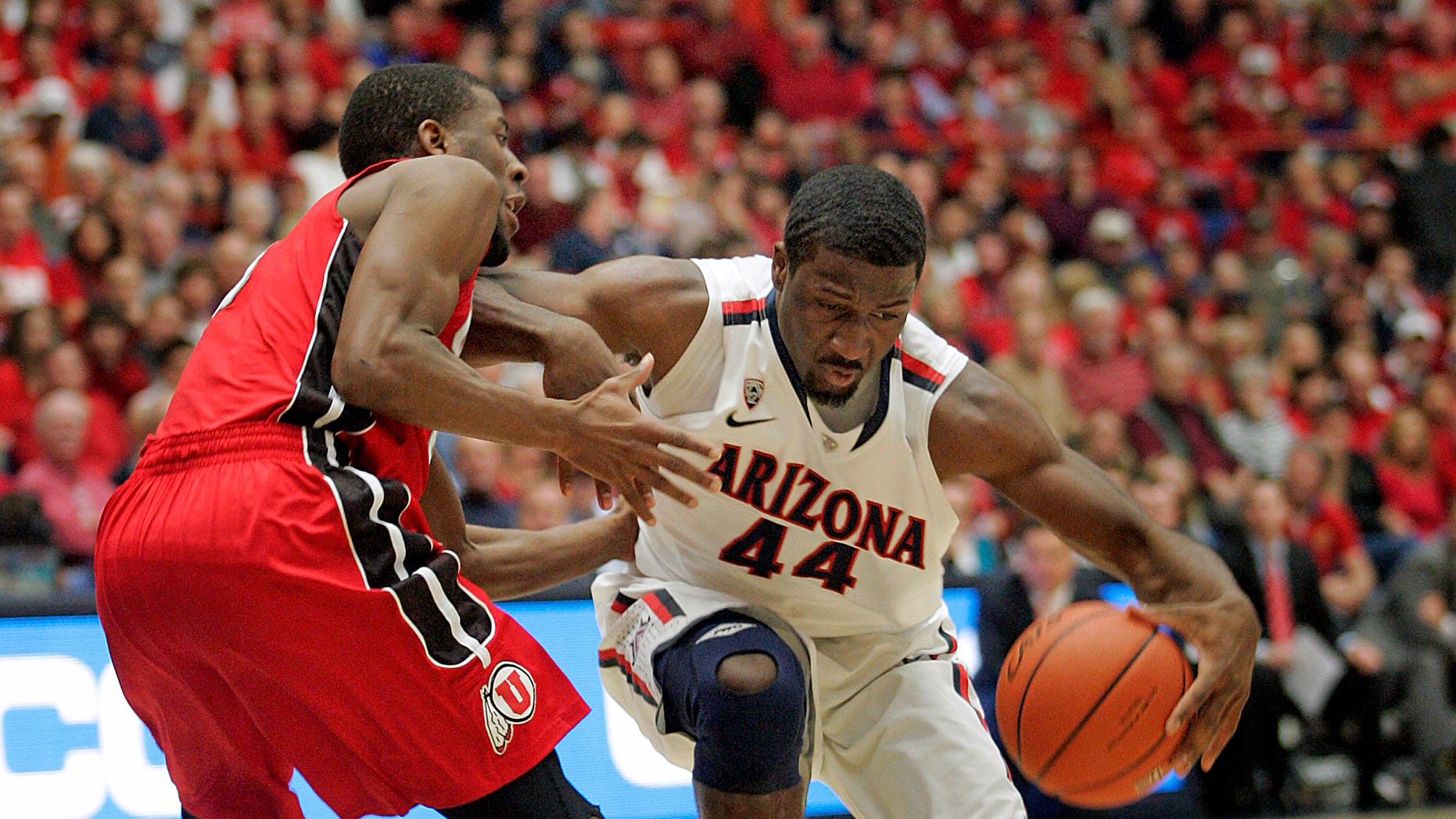 Arizona's Soloman Hill, (44) drives against the pressing defense of Utah's Jarred DuBois, left, during the first half of an NCAA college basketball game at McKale Center in Tucson, Ariz., Jan. 5, 2013. (AP Photo/John Miller)