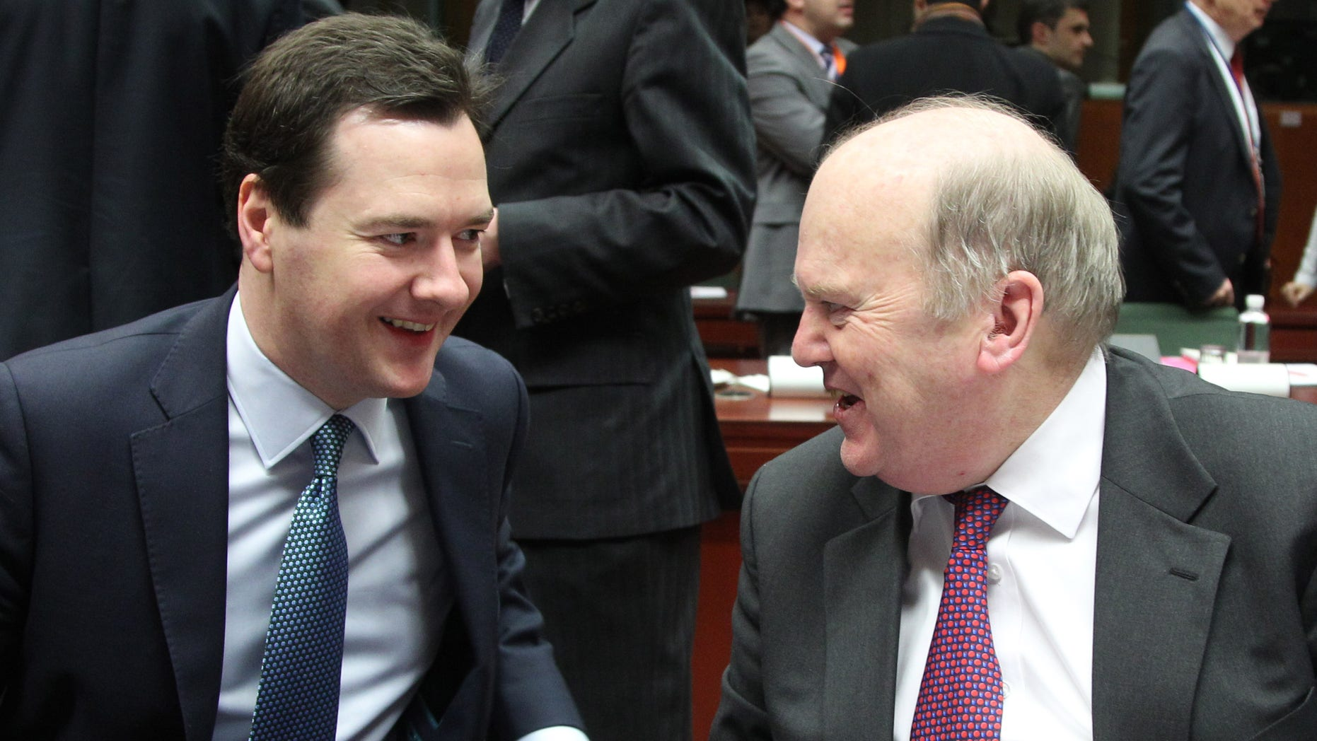 British Chancellor of the Exchequer George Osborne, left, talks with President of the EU rotating Council and Irish Finance Minister Michael Noonan during the EU finance ministers meeting, at the European Council building in Brussels, Tuesday, Feb. 12, 2013. Irish Finance Minister Michael Noonan has voiced his opposition to any proposal that the European Central Bank should intervene to get the value of the euro down. (AP Photo/Yves Logghe)