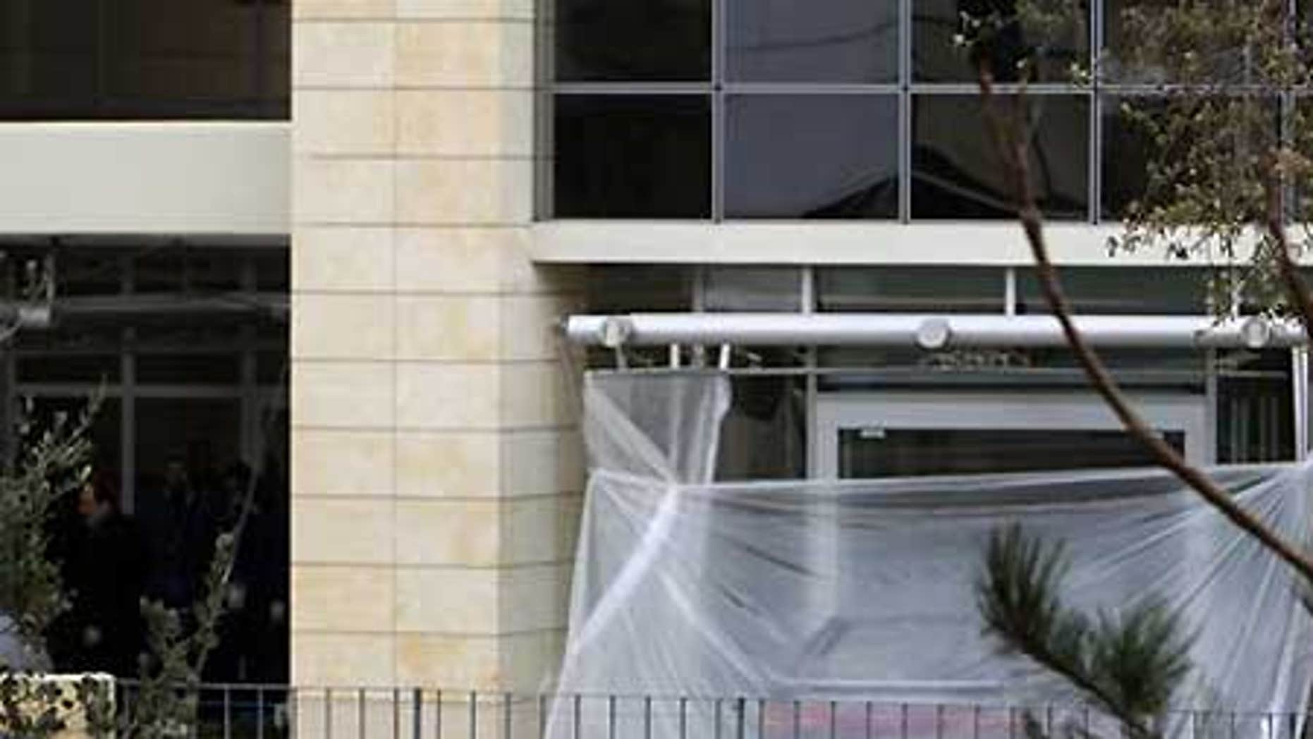 Feb. 18: Greek Police officers are seen, left, as a plastic sheet covers a parked car used in a foiled bomb attack at the Citibank offices in Athens.