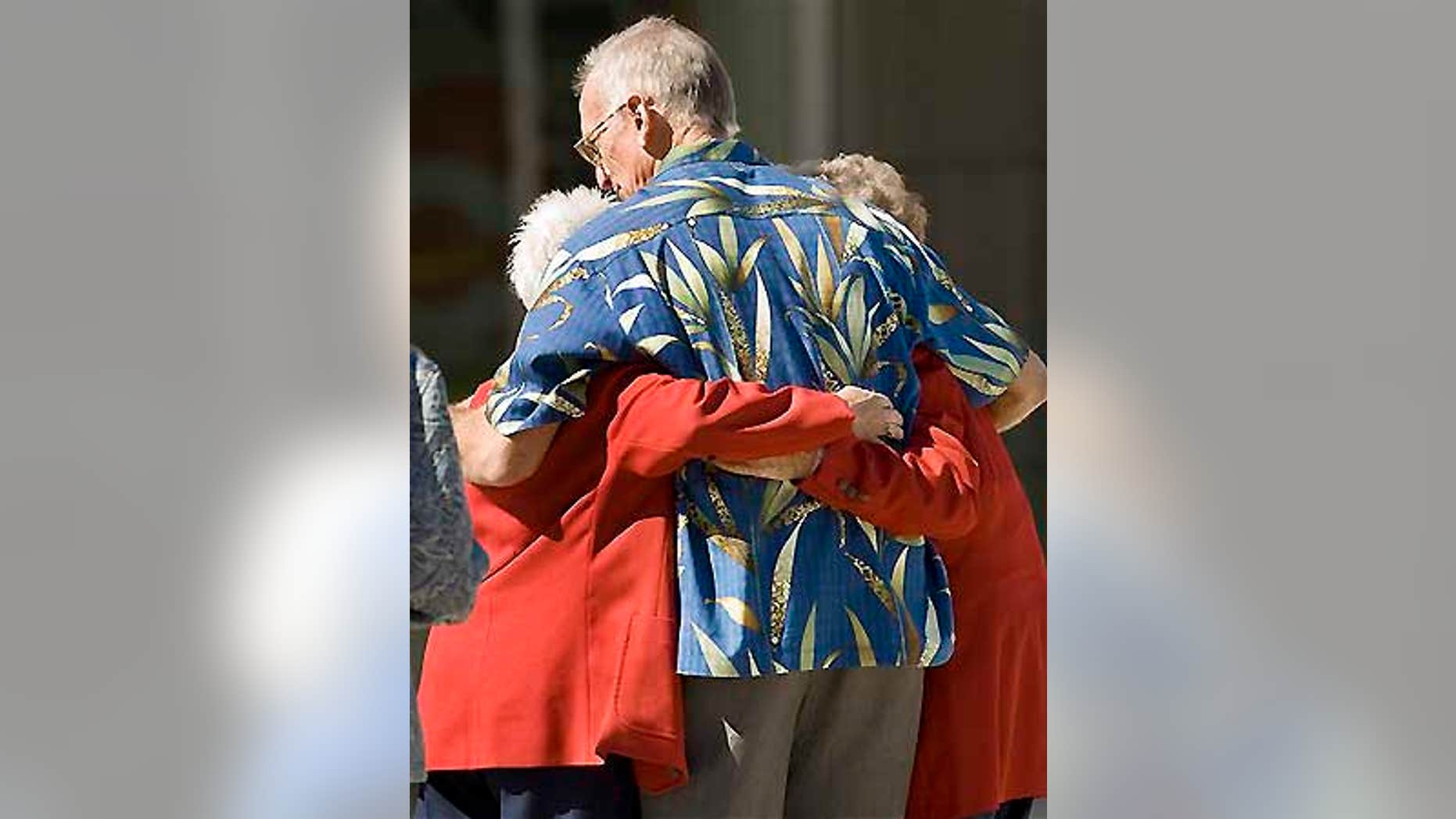 Two red-coated ushers at televangelist Robert H. Schuller's Crystal Catherdral get a hug after witnessing a man shoot himself in the church.