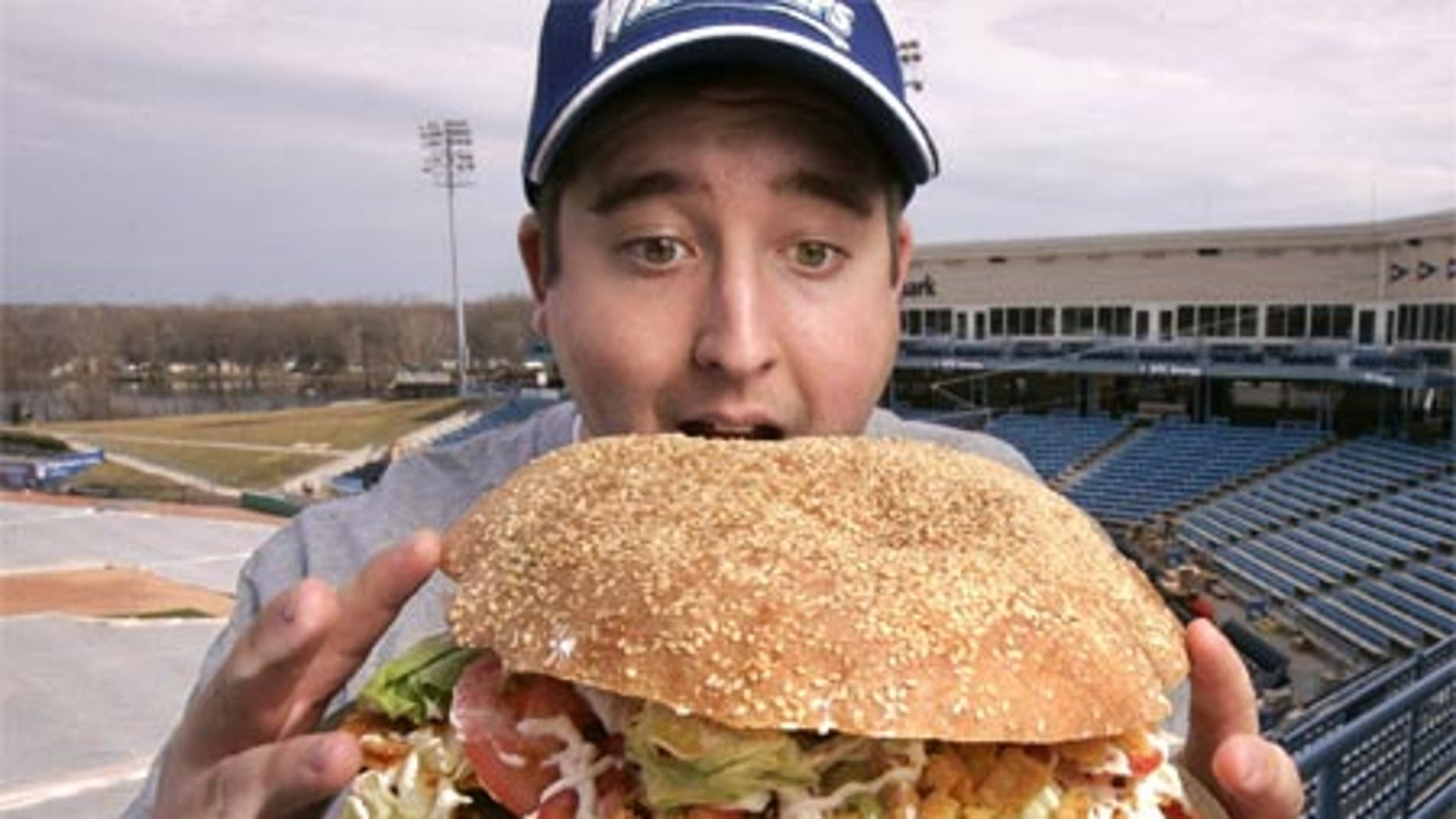 March 24: Josh Kowalczyk, an intern with the West Michigan Whitecaps, in Comstock Park, Mich. poses with the monster $20 burger.