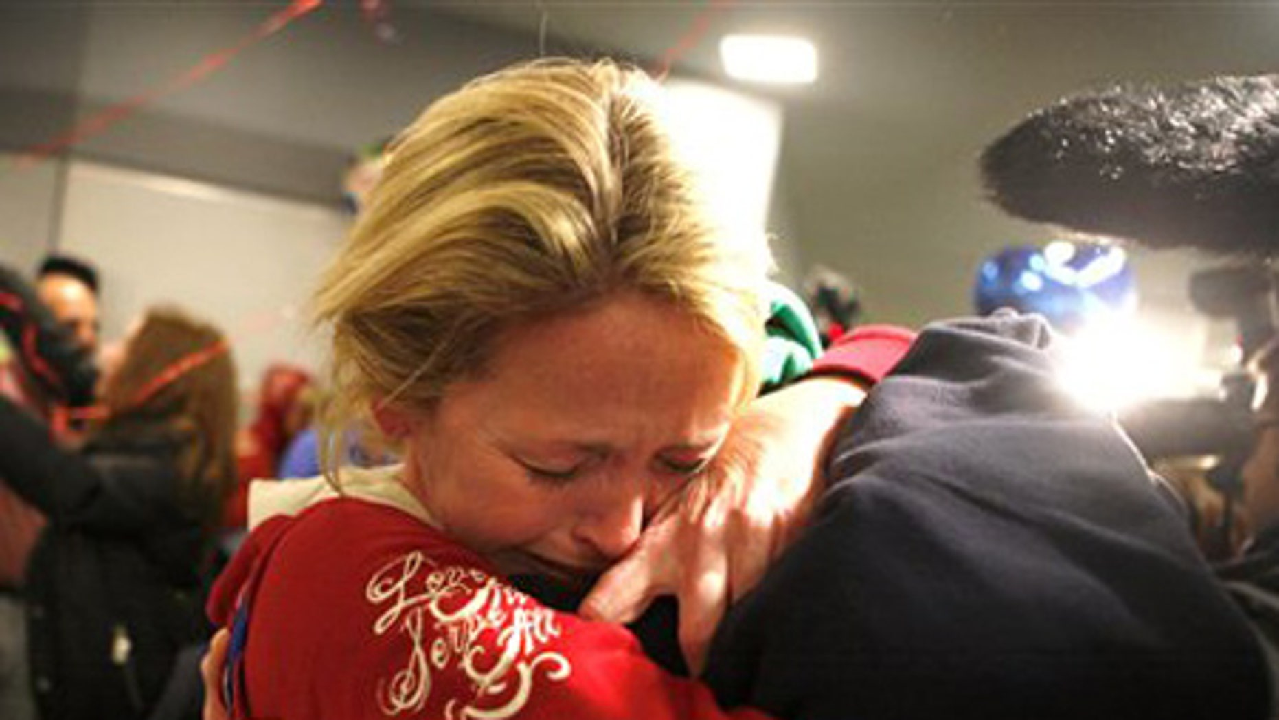 Jan. 15: Linda Callahan embraces her son as she and members of Trinity Methodist return from Haiti.