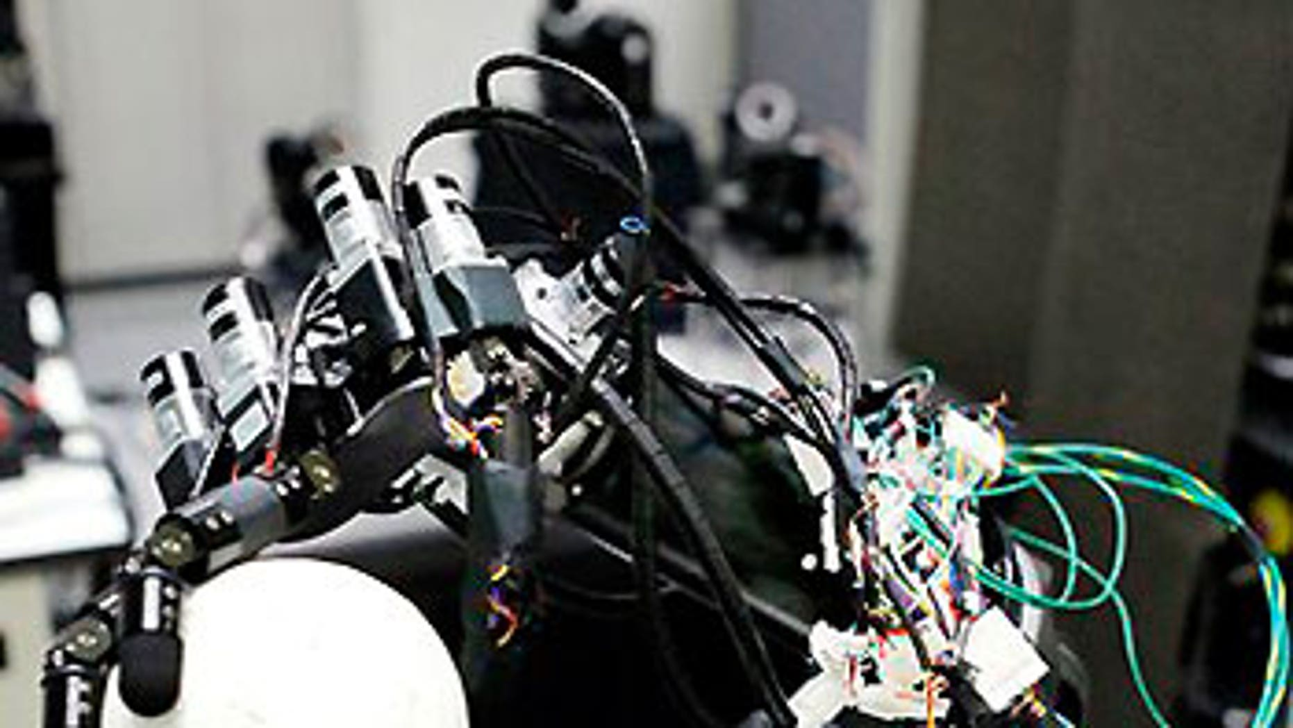 July 24: A pitching robot grips a ball made of polystyrene during its demonstration at the University of Tokyo.