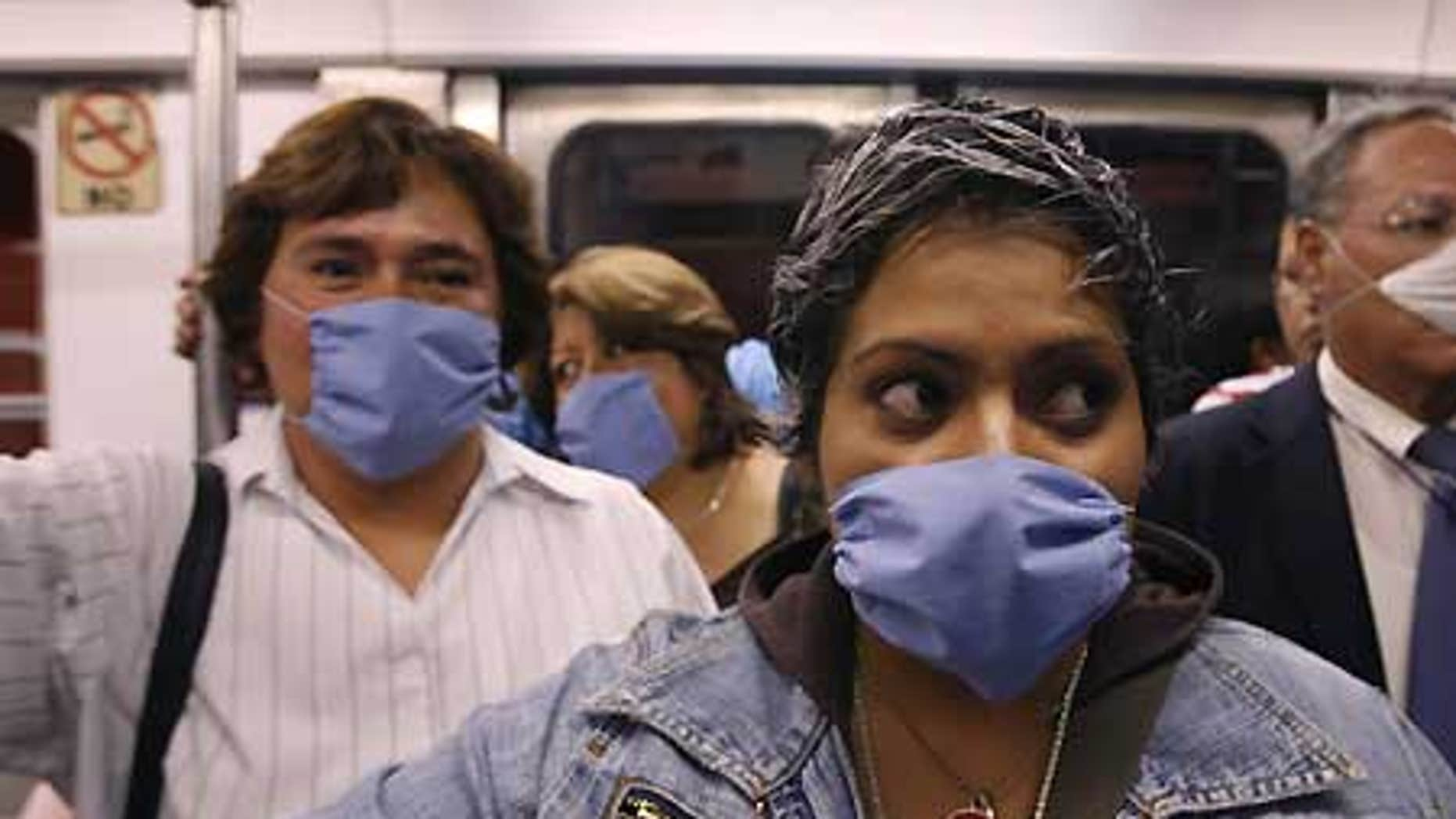 April 24: People wear surgical masks as a precaution against infection inside a subway in Mexico City.