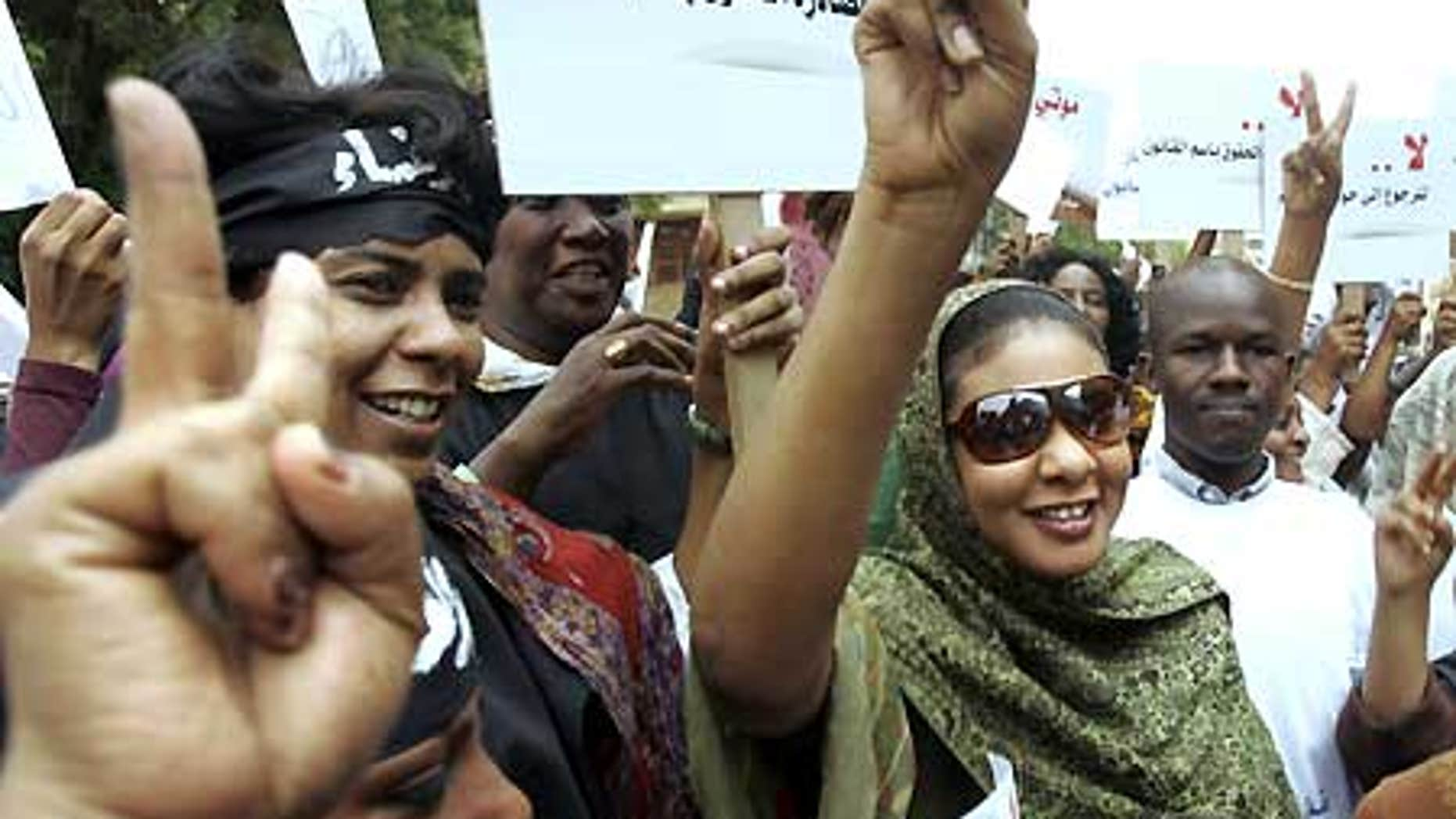 Aug. 4: Sudanese journalist Lubna Hussein, right, who faces 40 lashes on the charge of 'indecent dressing,' flashes a victory sign to her supporters.