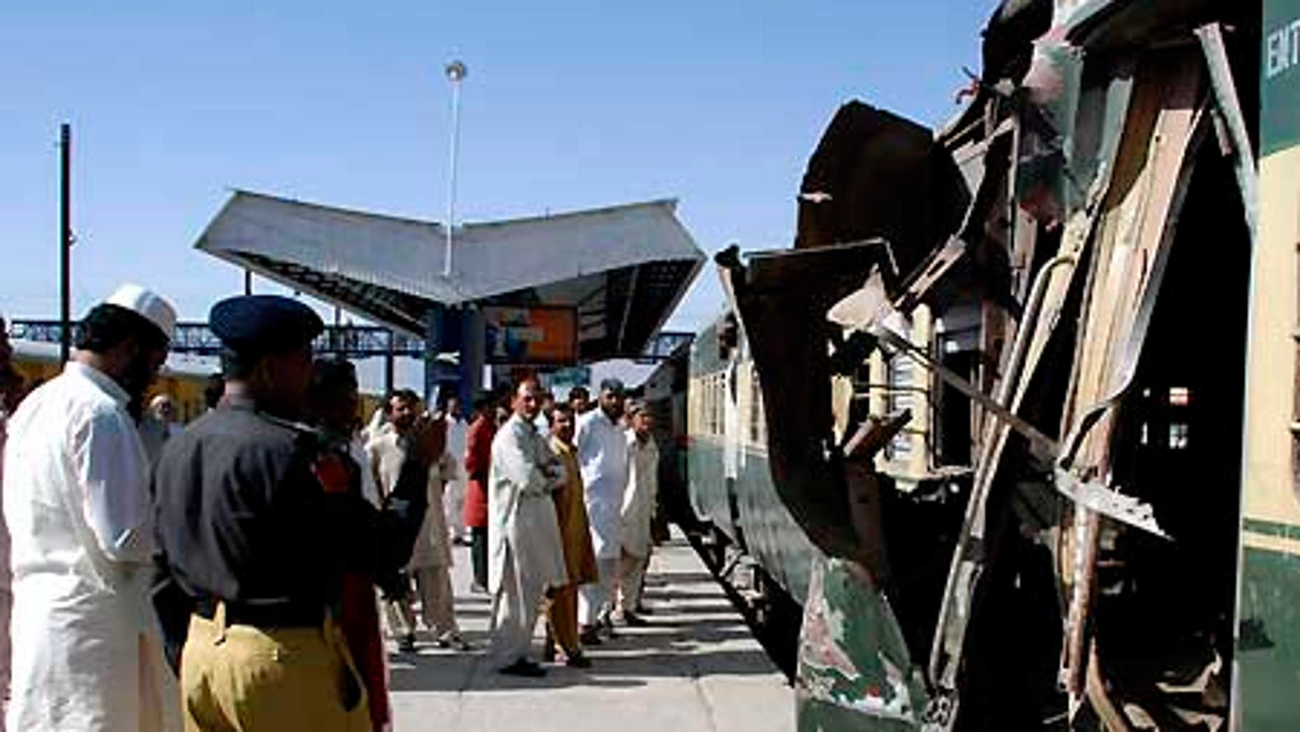 June 11: People look at a compartment of a passenger train damaged by a bomb blast in Quetta, Pakistan.