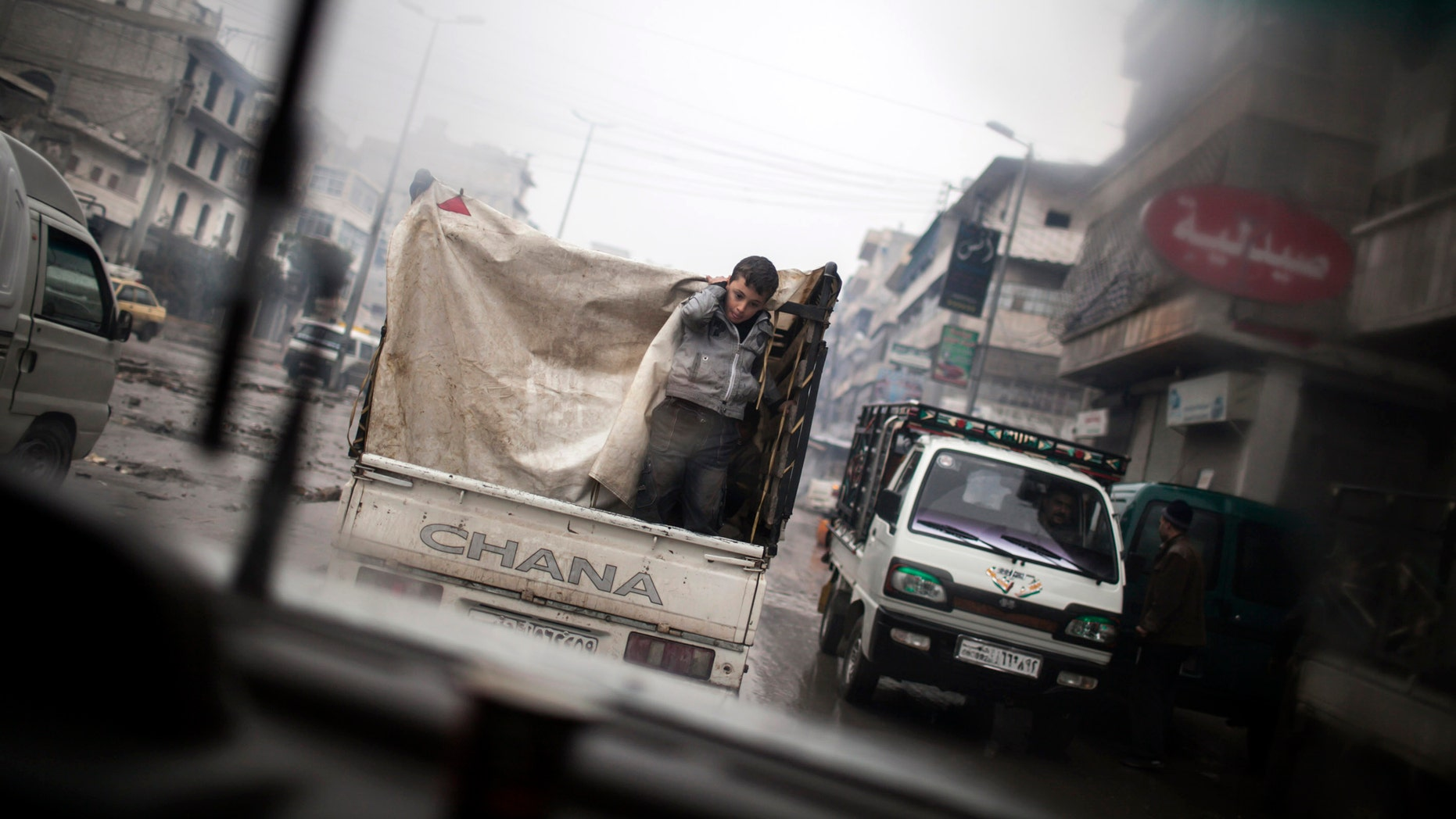 A boy is seen through a car window as he rides on the back of a truck in the streets of Aleppo, Syria, Saturday, Jan. 5, 2013. The revolt against President Bashar Assad that started in March 2011 began with peaceful protests but morphed into a civil war that has killed more than 60,000 people, according to a recent United Nations recent estimate. (AP Photo/ Andoni Lubaki)