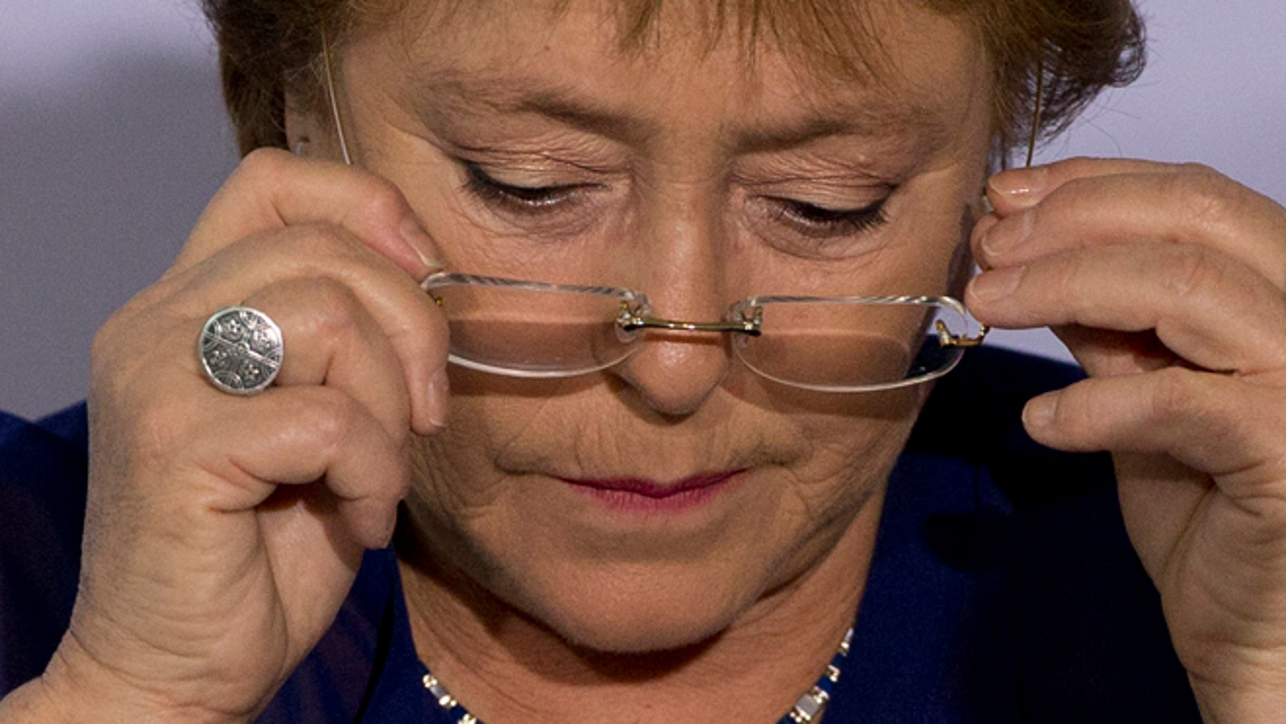 FILE - In this Dec. 9, 2014 file photo, Chile's President Michelle Bachelet puts on her glasses during a 2014 Iberoamerican Summit event in Veracruz, Mexico. Bachelets approval rating is at her lowest level ever, but she said Wednesday, April 8, 2015, that she doesn't care about her popularity, as shes focused on the well-being of Chile and pushing forward needed reforms. (AP Photo/Rebecca Blackwell, File)