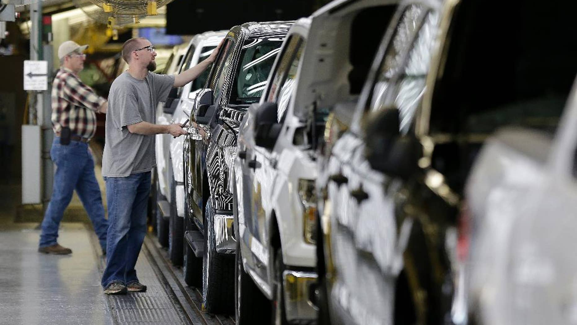 FILE - In this March 13, 2015, file photo, a worker inspects a new 2015 aluminum-alloy body Ford F-150 truck at the company's Kansas City Assembly Plant, in Claycomo, Mo. The Commerce Department releases its October report on orders for durable goods, items expected to last at least three years, on Wednesday, Nov. 25, 2015. (AP Photo/Charlie Riedel, File)