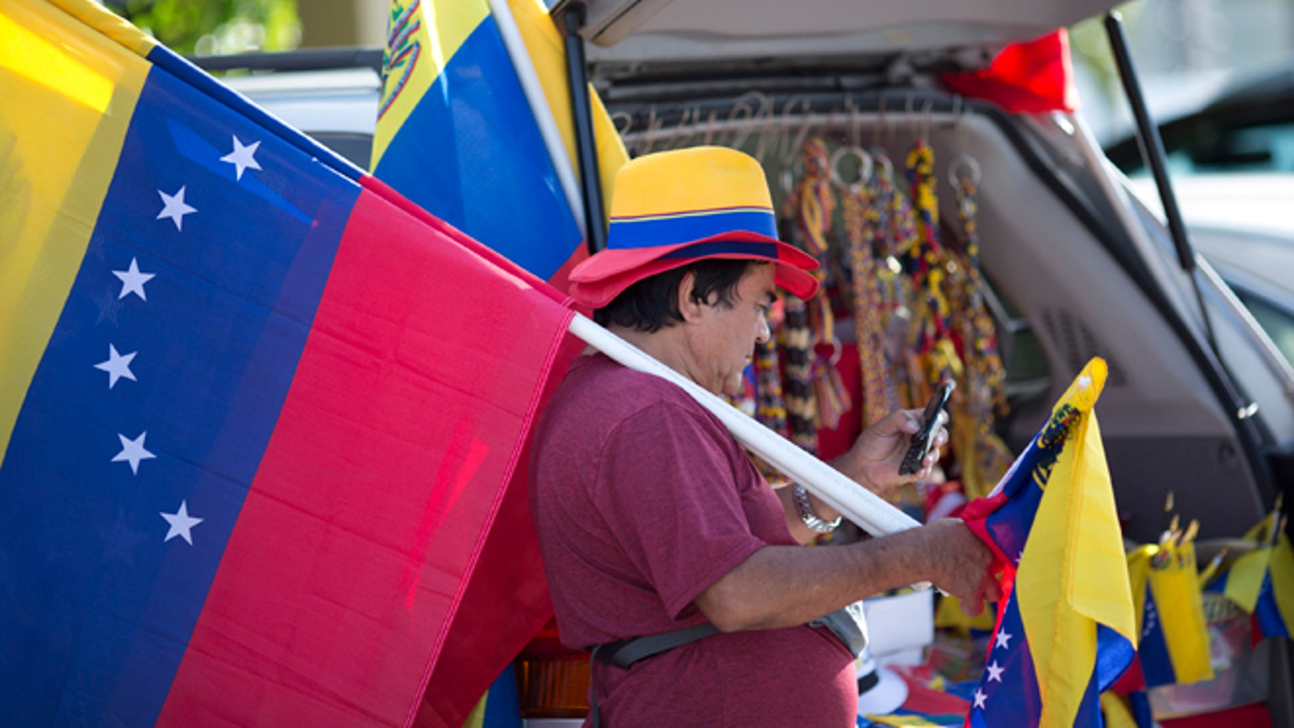 Xidmara Landaeta carries his country's flag, offering them for sale, as Venezuelans from South Florida prepare for their bus trip to Washington, Thursday, May 8, 2014, in Doral, Fla. They are rallying to ask the Congress and President Barack Obama to impose economic sanctions and travel restrictions to the Venezuelan government officials because of presumed human right violations in the South American country. Organizers said they expect Venezuelans from 19 states will meet in Washington on Friday to demonstrate in front of the White House, Congress and the Organization of American States.  (AP Photo/J Pat Carter)