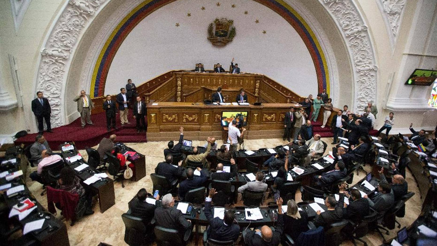 FILE - In this Jan. 6, 2016, file photo, lawmakers vote on the daily agenda during the first National Assembly session in Caracas, Venezuela. The country's attorney general said Saturday, July 30, that the National Assembly is now illegally constituted because in recent days it swore in three members who'd been ruled out by the government-friendly Supreme Court. (AP Photo/Fernando Llano, File)