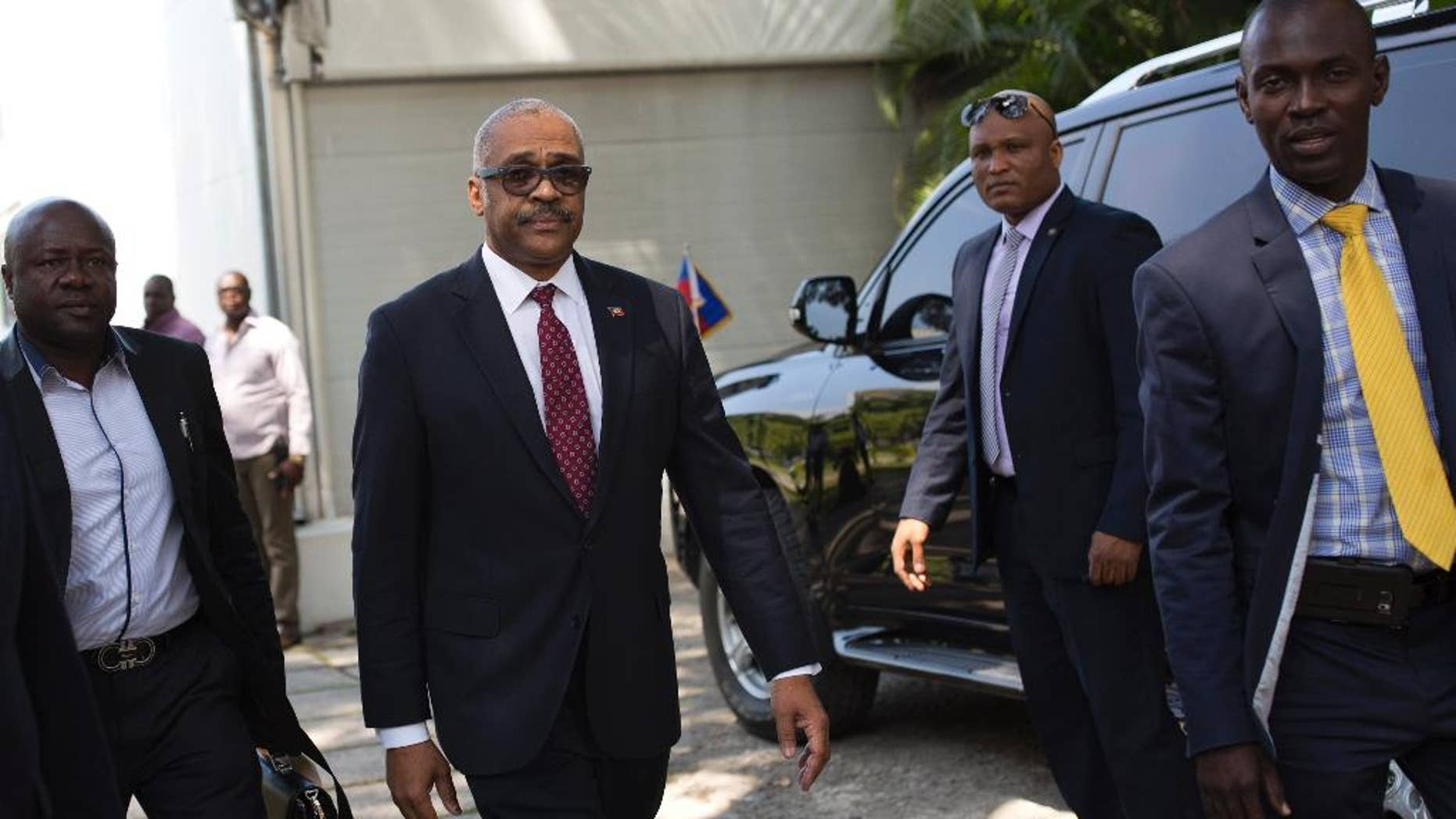FILE - In this Feb. 24, 2017, file photo, Haiti's newly nominated Prime Minister Dr. Jack Guy Lafontant, center, arrives at the national palace for his nomination ceremony in Port-au-Prince, Haiti. Lafontant, a gastroenterologist and head of the Rotary Club in the commercial district of Petionville has been ratified as Haiti's Prime Minister on Tuesday, March 21. (AP Photo/Dieu Nalio Chery, File)