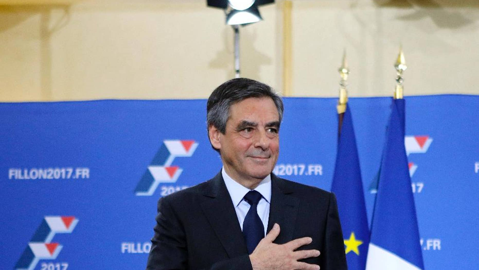 Francois Fillon puts his hand on his hear after delivering a speech following the conservative presidential primary Sunday, Nov. 27, 2016 in Paris. Fillon won France's first-ever conservative presidential primary Sunday after promising drastic free-market reforms and a crackdown on immigration and Islamic extremism, beating a more moderate rival who had warned of encroaching populism. (AP Photo/Kamil Zihnioglu)