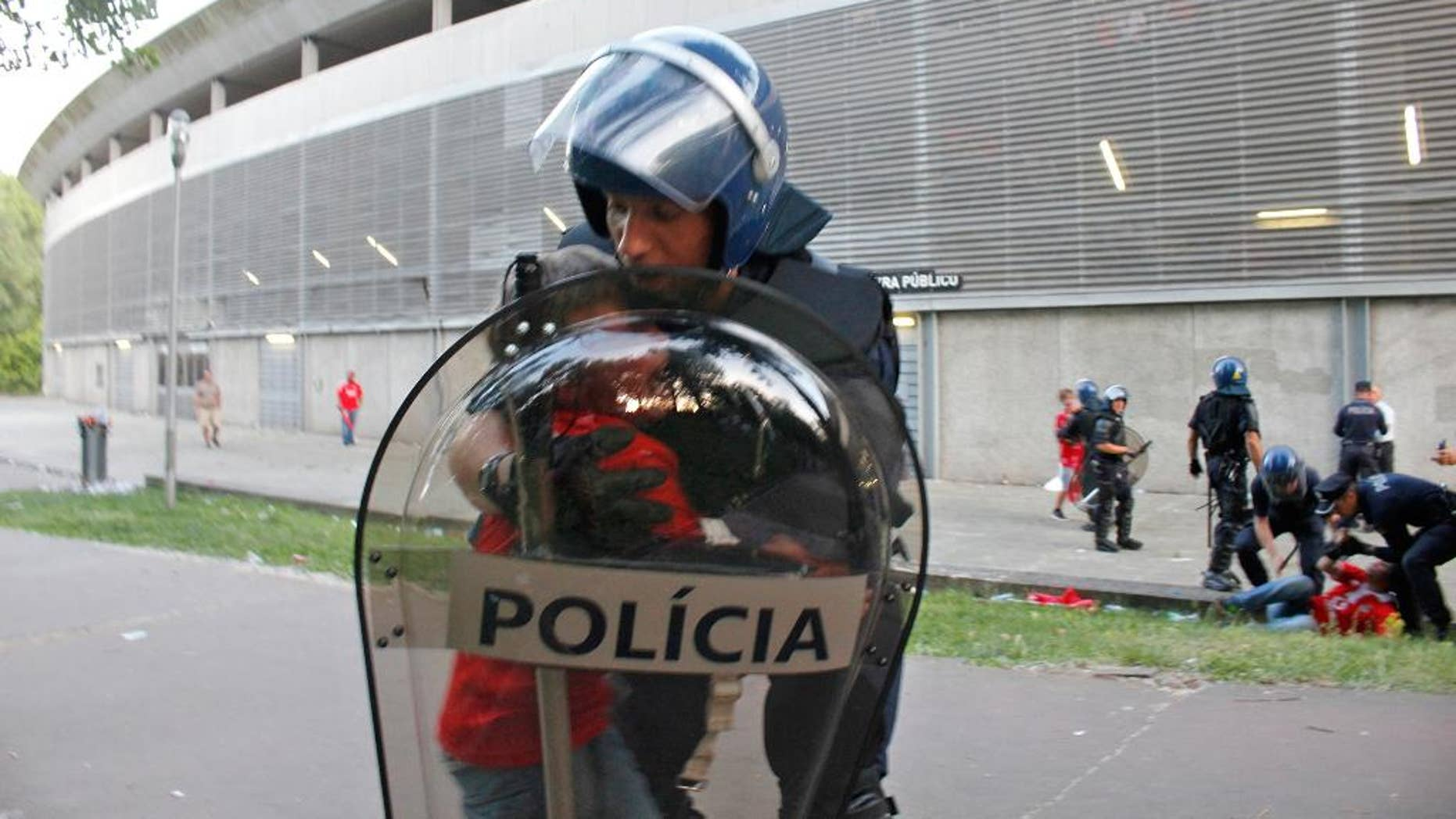 In this May 17 2015 file photo, a riot policeman holds a crying boy as his father is attacked by other policemen with batons, right, outside of a stadium, in Guimaraes, Portugal. Portugal's public prosecutor has filed charges Tuesday April 12, 2016,  that could bring a prison sentence of more than 10 years against a policeman who beat a middle-aged football fan in front of his two young sons, with the video of the incident causing a national scandal. (AP Photo/Delfim Machado)
