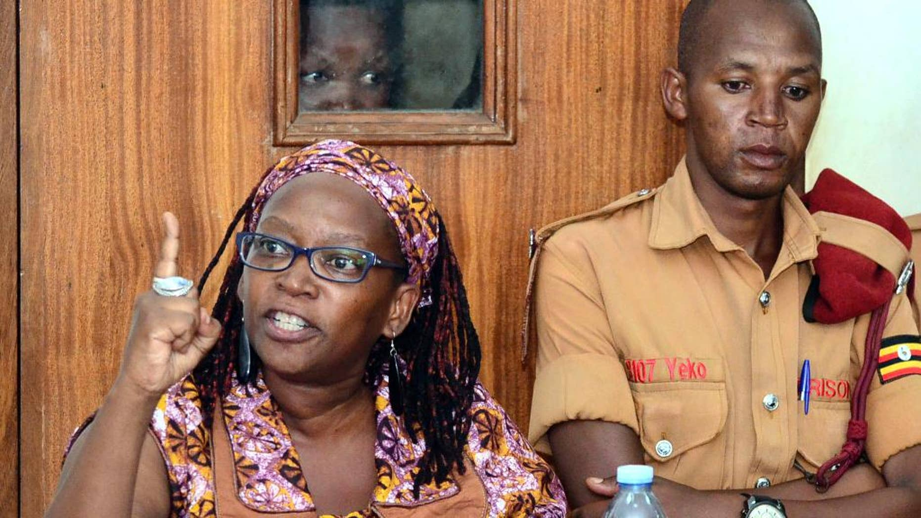 """In this photo taken on Monday April 10, 2017, Makerere University researcher Dr Stella Nyanzi, left, gestures in the dock at Buganda Road Court in the capital Kampala, Uganda. A Ugandan academic detained for calling the country's president """"a pair of buttocks"""" resisted attempts to forcibly carry out psychiatric tests on her, her attorney said Thursday, April 13 describing the alleged incident as an attack on her dignity.(AP Photo)"""