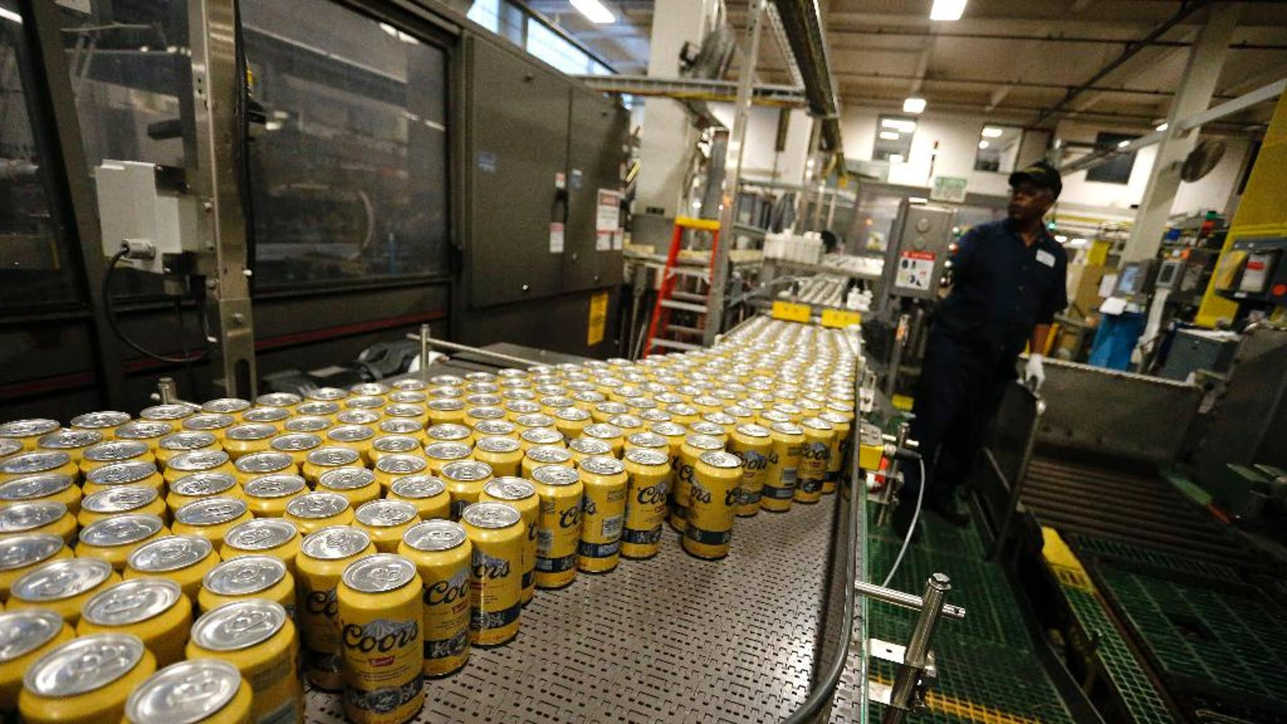 In this March 11, 2015 photo, newly-filled and sealed cans of Coors Banquet beer move along on a conveyor belt at the MillerCoors Brewery, in Golden, Colo. The Labor Department releases the Producer Price Index for March on Tuesday, April 14, 2015. (AP Photo/Brennan Linsley)