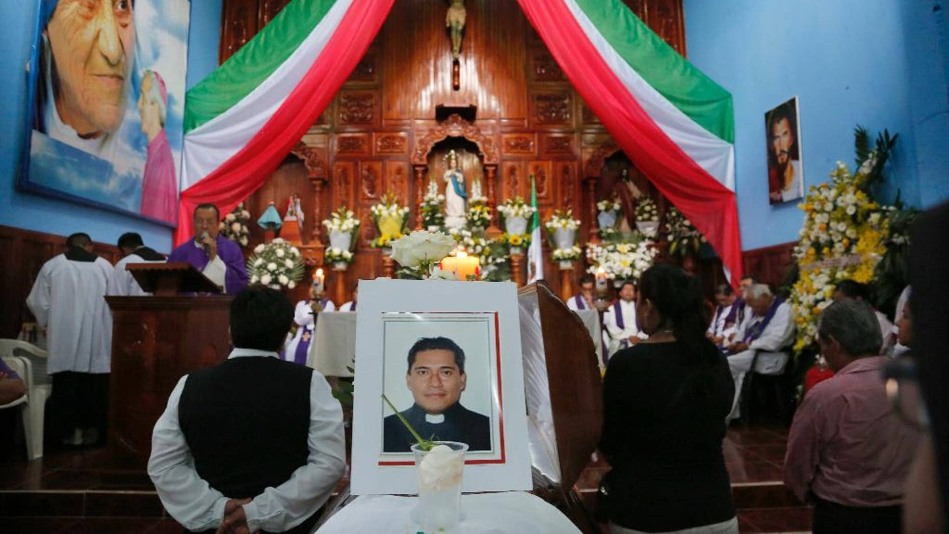 FILE - In this Sept. 21, 2016 file photo, people gather at Our Lady of Asuncion Church in Paso Blanco, Veracruz state, Mexico, for the funeral Mass of Rev. Jose Alfredo Suarez de la Cruz, one of two priests who was found bound and shot to death along a roadside on Sept. 19.  Mexican authorities arrested a suspect in the abduction and murder of the two priests in Veracruz state last month. Mexico City prosecutors say in a statement released Monday, Oct. 17, 2016, that the unidentified person was detained Oct. 13 along with another person after they allegedly car-jacked a couple in the capital. (AP Photo/Marco Ugarte, File)
