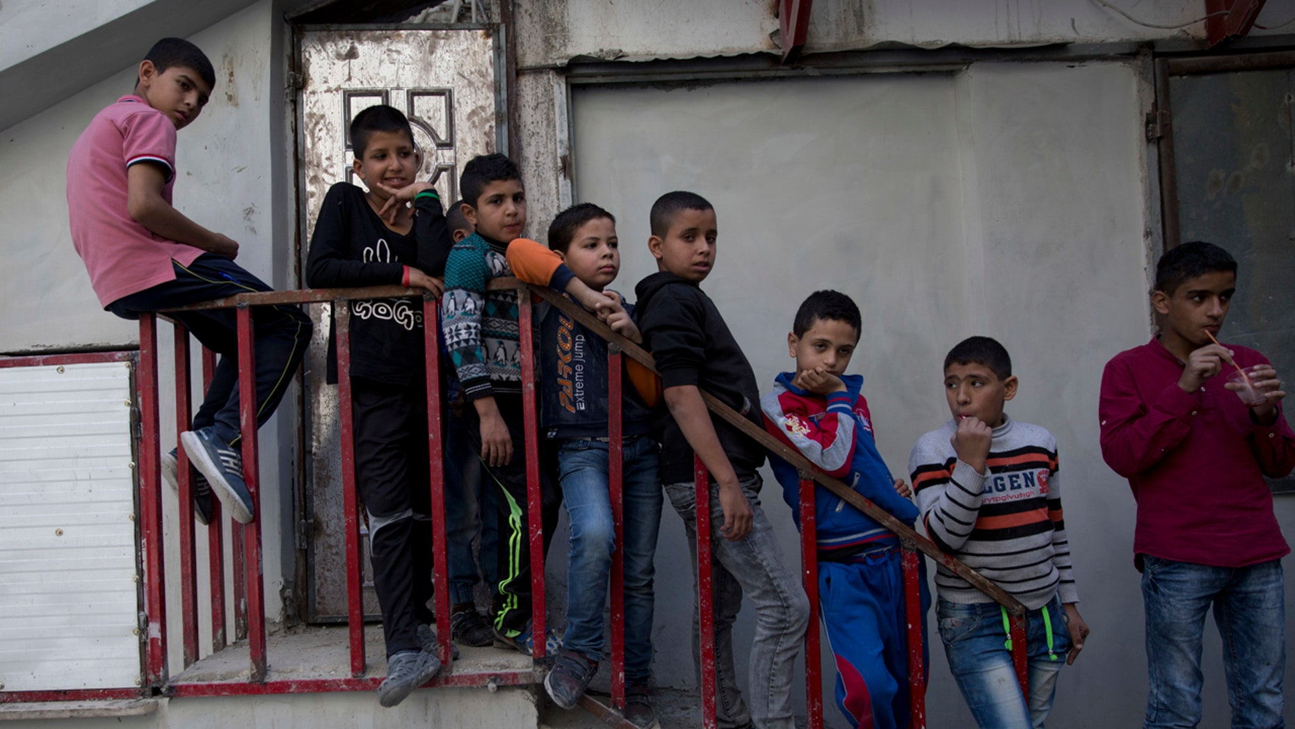 In this photo taken Thursday, Nov. 10, 2016, boys watch Palestinian men who are wanted by the Palestinian Authority security while talking to the Associated Press, in Balata refugee camp, in the West Bank.