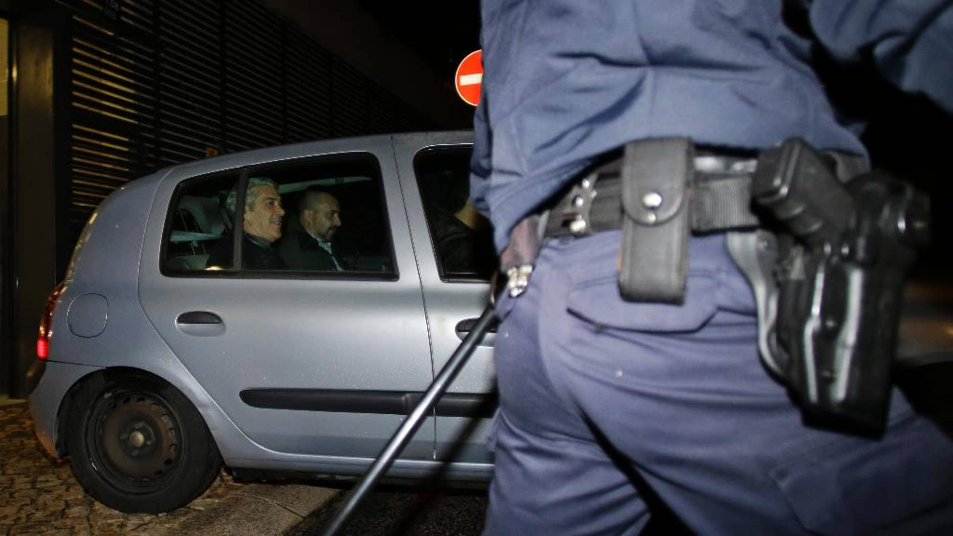 Portugal's former Prime Minister Jose Socrates, at left in the back seat of the car, leaves a court in a Portuguese police car after being questioned, in Lisbon, Sunday, Nov. 23, 2014.  Socrates, who was Portugal's center-left Socialist Prime Minister from 2005 to 2011, was due in a Lisbon court Sunday for a closed-door interrogation, deciding whether he should answer charges of alleged corruption, money-laundering and tax fraud. (AP Photo/Francisco Seco)
